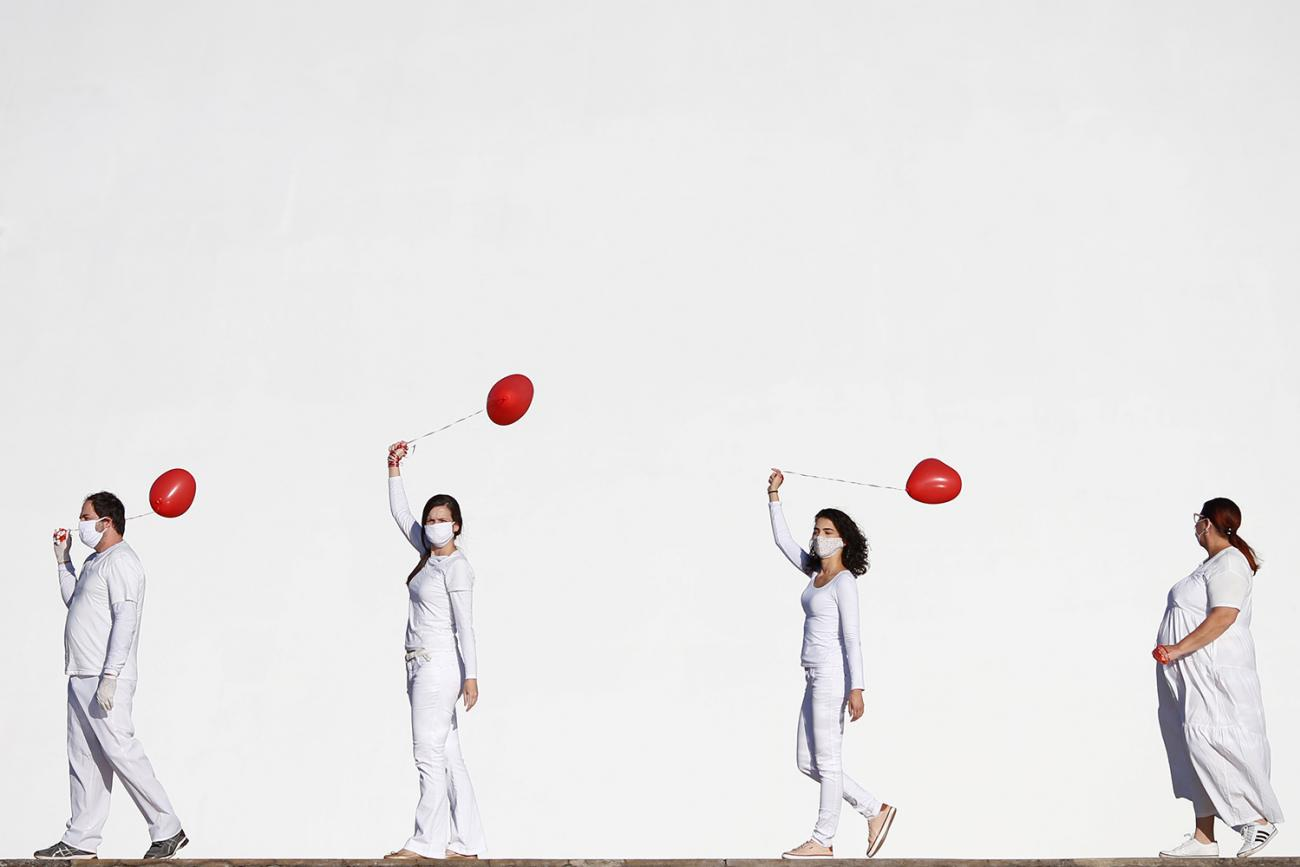 Artists perform with red balloons at a protest in honor of people who died from coronavirus disease (COVID-19) during its outbreak in Brasilia, Brazil, on June 1, 2020. The photo shows four artists dressed in white walking in front of a massive white backdrop. Each holds a red balloon. REUTERS/Adriano Machado