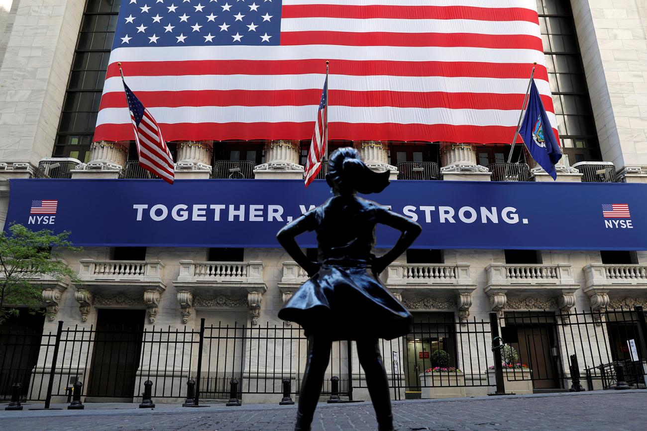 """The """"Fearless Girl"""" statue is seen outside the New York Stock Exchange following first trading session since its March coronavirus lockdown in the Manhattan borough of New York City on May 26, 2020. The photo shows the statue with a huge American flag in the background. REUTERS/Mike Segar"""