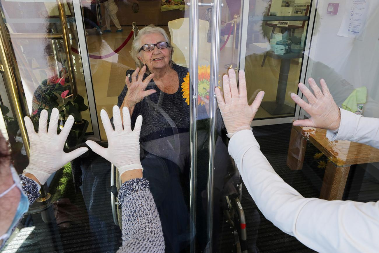 """A resident named Mrs. Oury reacts as her daughters wave behind a glass during a visit at """"Les Figuiers"""" retirement home amid the coronavirus outbreak in Villeneuve-Loubet, France, on April 23, 2020. The photo shows a woman from behind glass while two others stand with their backs to the camera looking in. They all have their hands up. REUTERS/Eric Gaillard"""