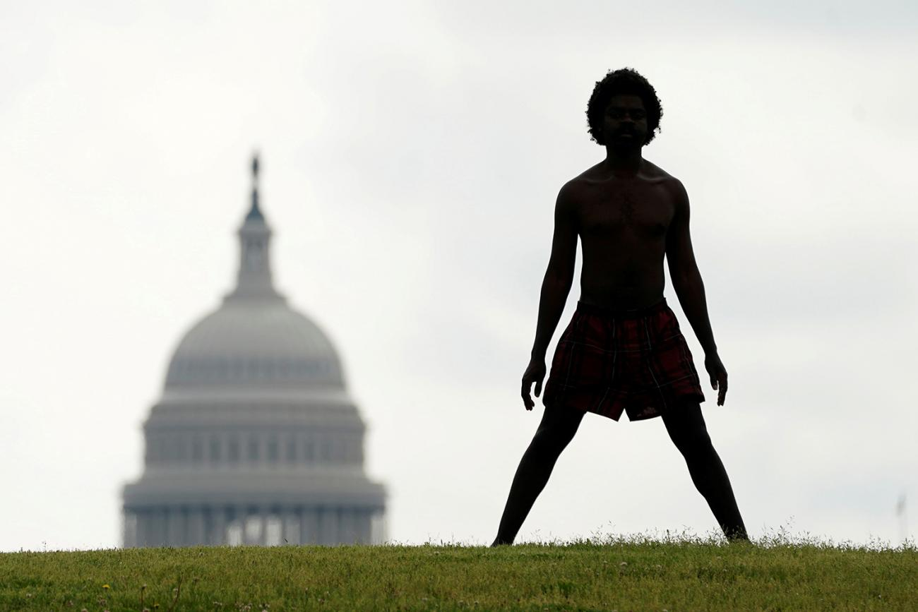 With the dome of the U.S. Capitol in the background, a homeless man named Damu stretches on the National Mall in Washington, U.S., May 27, 2020. The photo is striking, with a man in silhouette standing on a hill with his legs spread wide. in the background slightly to his left is the congressional building. REUTERS/Kevin Lamarque