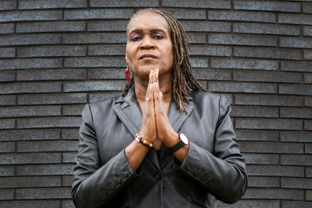 Minneapolis City Council Vice President Andrea Jenkins, who gave this interview. The photo shows the council vice president standing in front of a slate-colored brick wall with her hands together looking at the camera. IMAGE from Brooke Ross Photography