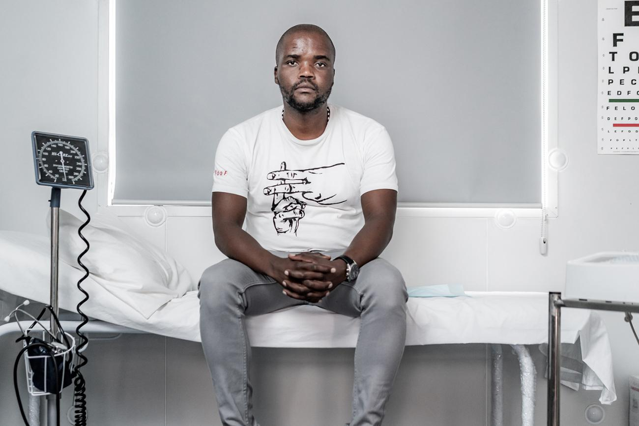 Goodman Makanda, who's involved in efforts to make tuberculosis and COVID-19 testing more acceptable and accessible for South African men, in Khayelitsha, Cape Town, South Africa, on March 24th 2019. The photo shows a man sitting in a clinic with various monitors and equipment. An eye exam is visible on the wall. MSF/Jelle Krings