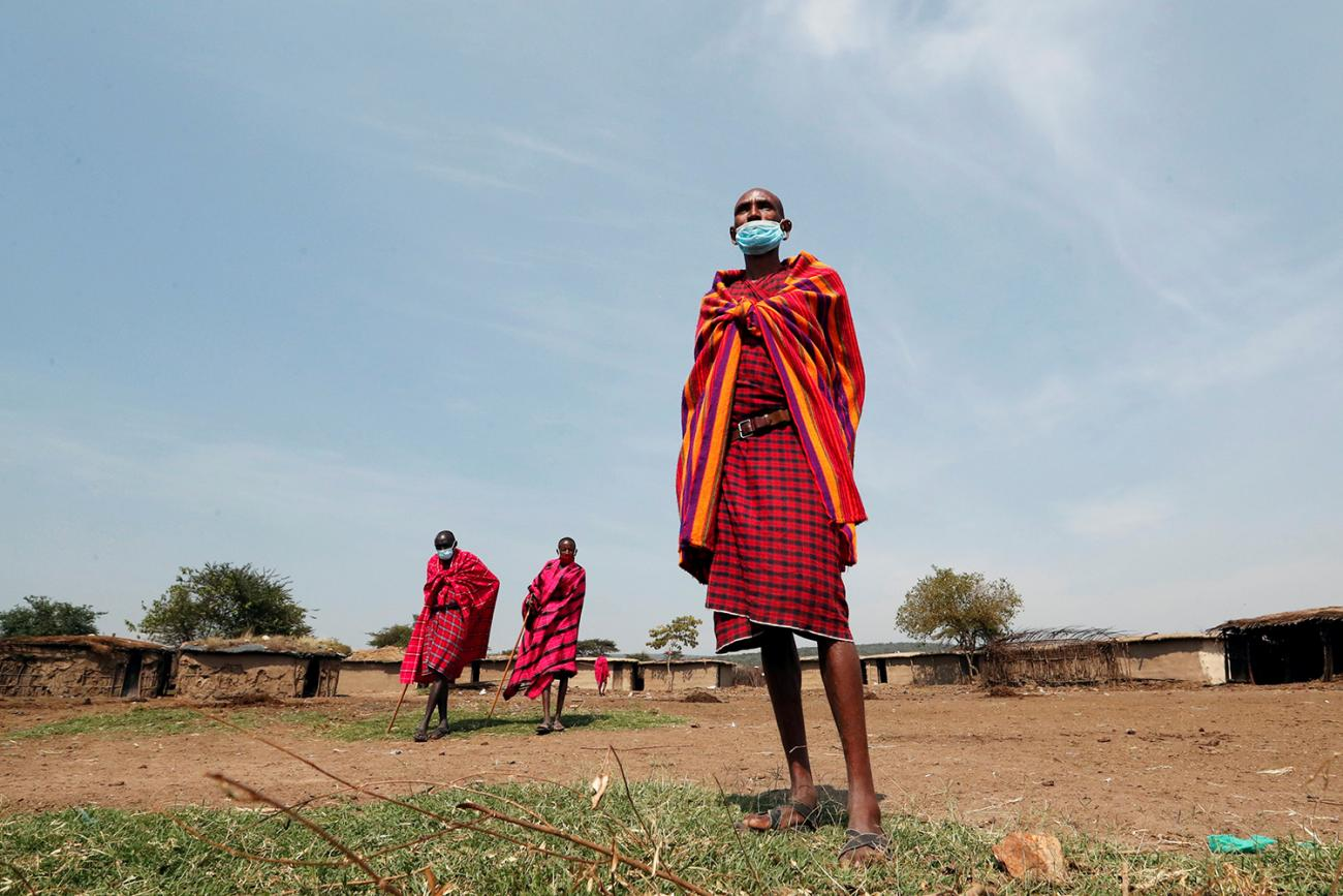 Maasai elders, wearing traditional clothes and facemasks due to coronavirus, gather within the Orboma Manyatta in Sekenani, near the Maasai Mara game reserve in Kenya, on August 10, 2020. This is a striking photo that shows a number of the elders in brightly colored reddish clothing on a clear day against a backdrop of what appears to be a village. REUTERS/Thomas Mukoya