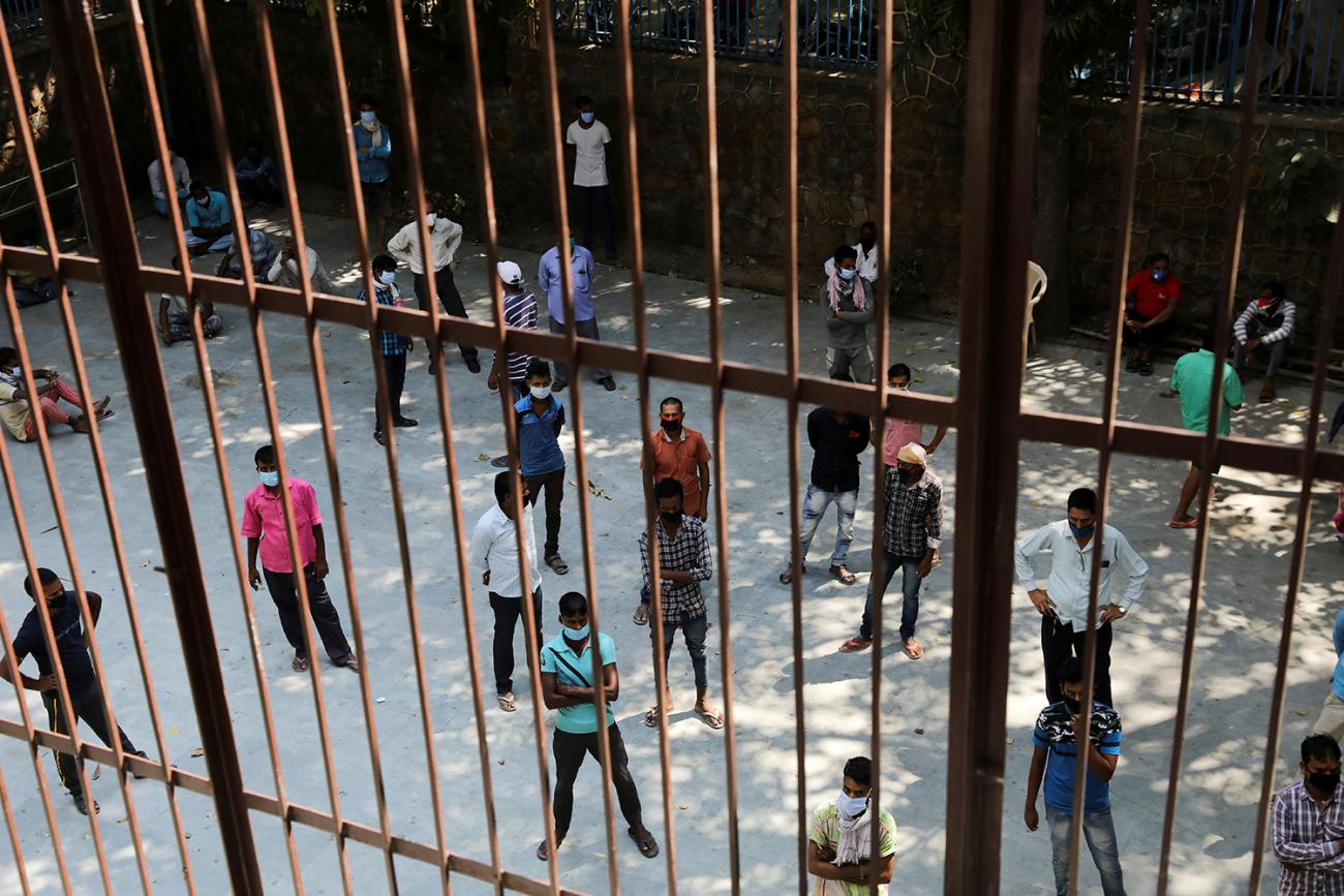 People wearing protective face masks wait for their rapid antigen test results outside a community center, amidst the spread of coronavirus in New Delhi, India, on September 17, 2020. The photo shows a large crowd of people from behind the bars of an iron fence. REUTERS/Anushree Fadnavis