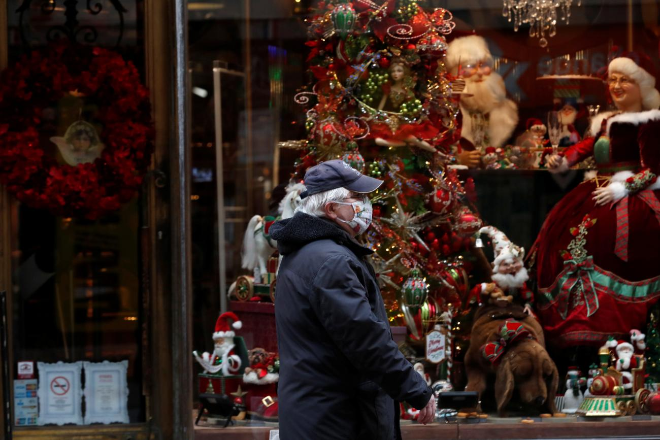 An elderly  man wearing a protective face mask walks in front of a Christmas store display in downtown Budapest, after Hungarian government imposed a nationwide lockdown to contain the spread of the coronavirus disease (COVID-19)