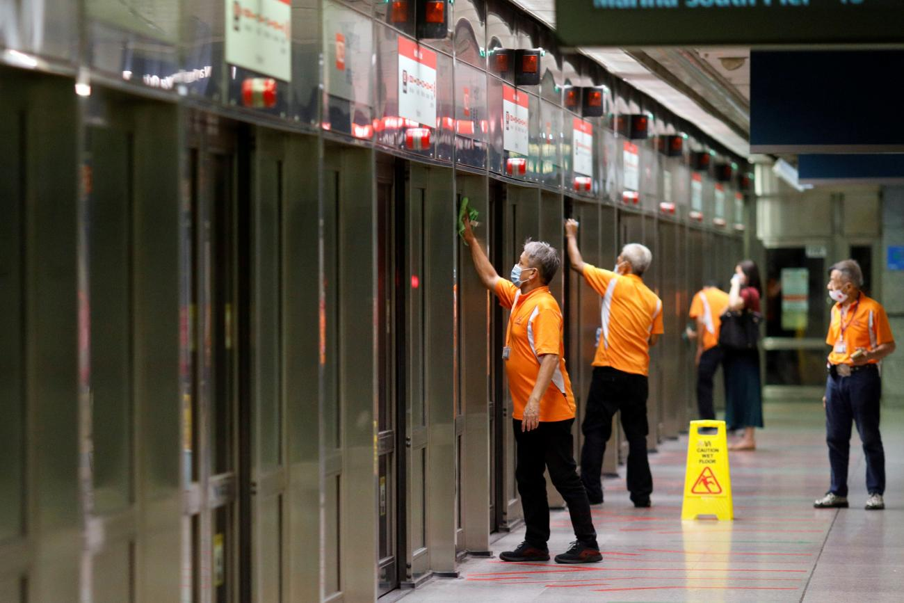 Workers wipe down doors at a train station during the coronavirus disease outbreak in Singapore on August 17, 2020.