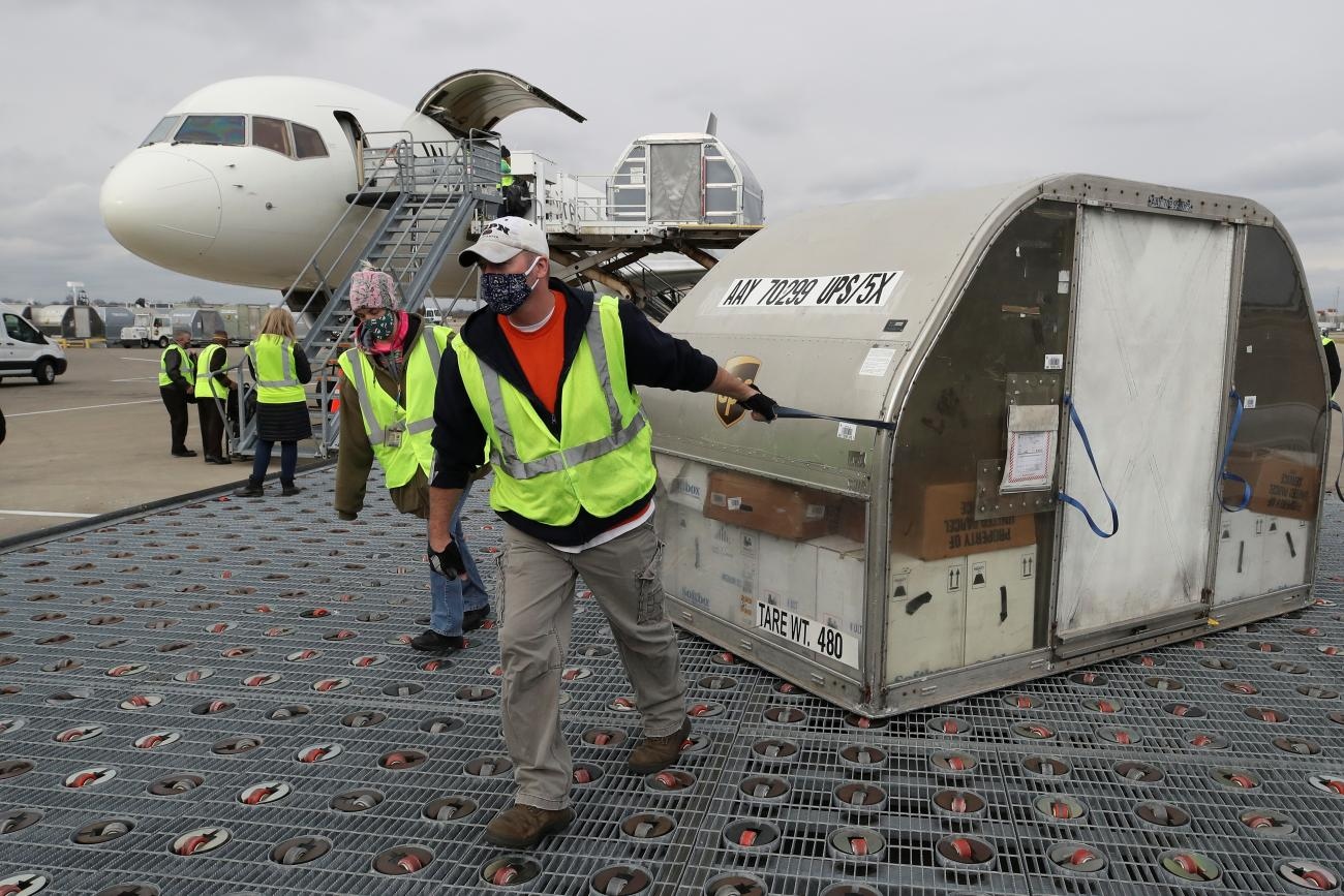 UPS employees move one of two shipping containers of the Pfizer COVID-19 vaccine on ramp at Louisville Muhammad Ali International Airport in Louisville, Kentucky, December 13, 2020.