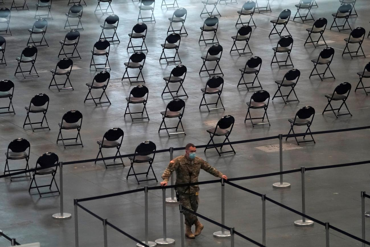 """A National Guard soldier looks on as people stand in line at the Jacob K. Javits Convention Center Vaccination Center as Governor Andrew M. Cuomo announces the start of the statewide """"Vaccinate NY"""" ad campaign to encourage all New Yorkers to get vaccinated, in New York City, New York, U.S. April 6, 2021."""