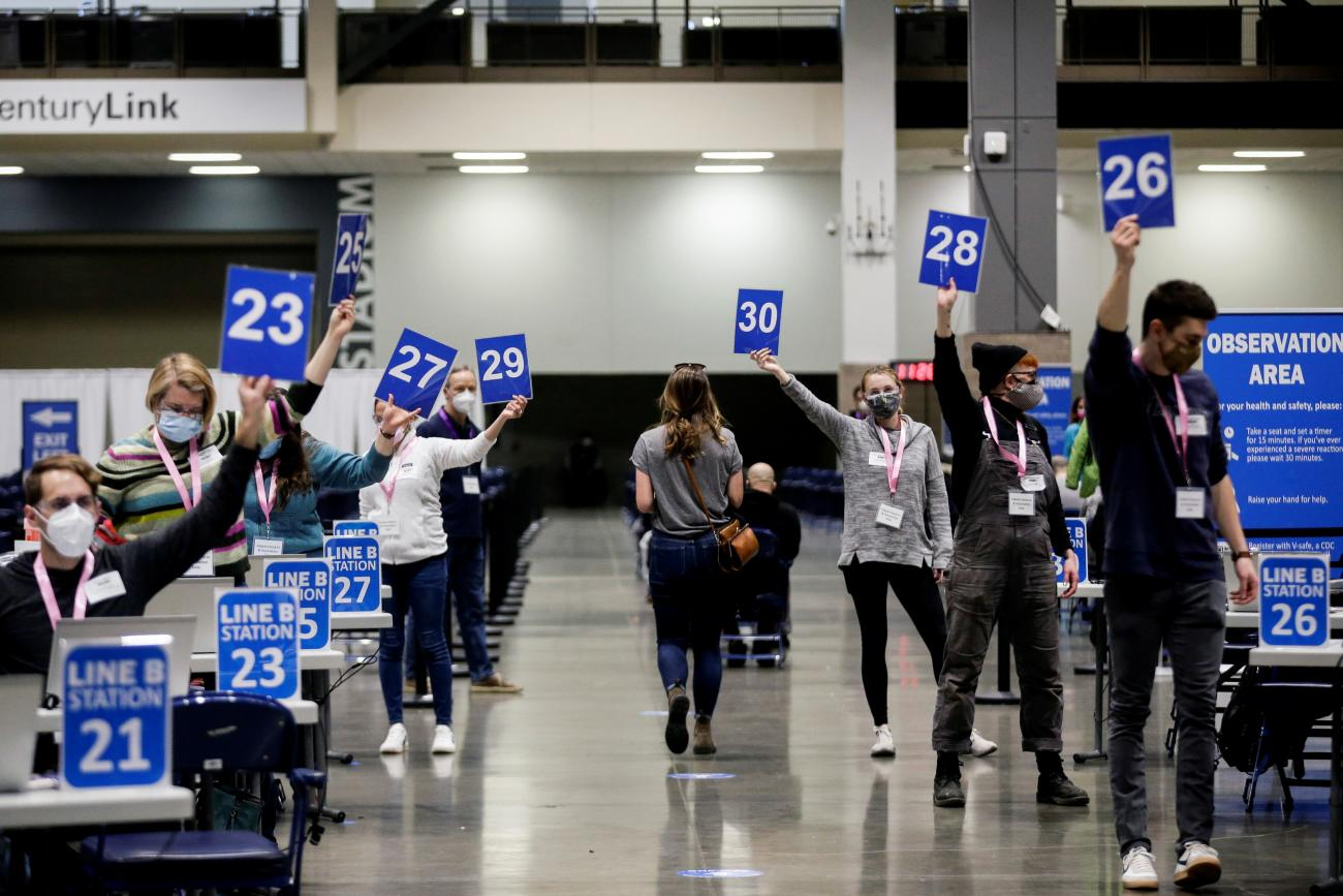 Workers hold up their station signs to signal they are ready for a patient at a coronavirus disease (COVID-19) vaccination site at Lumen Field Event Center in Seattle, Washington on March 13, 2021.