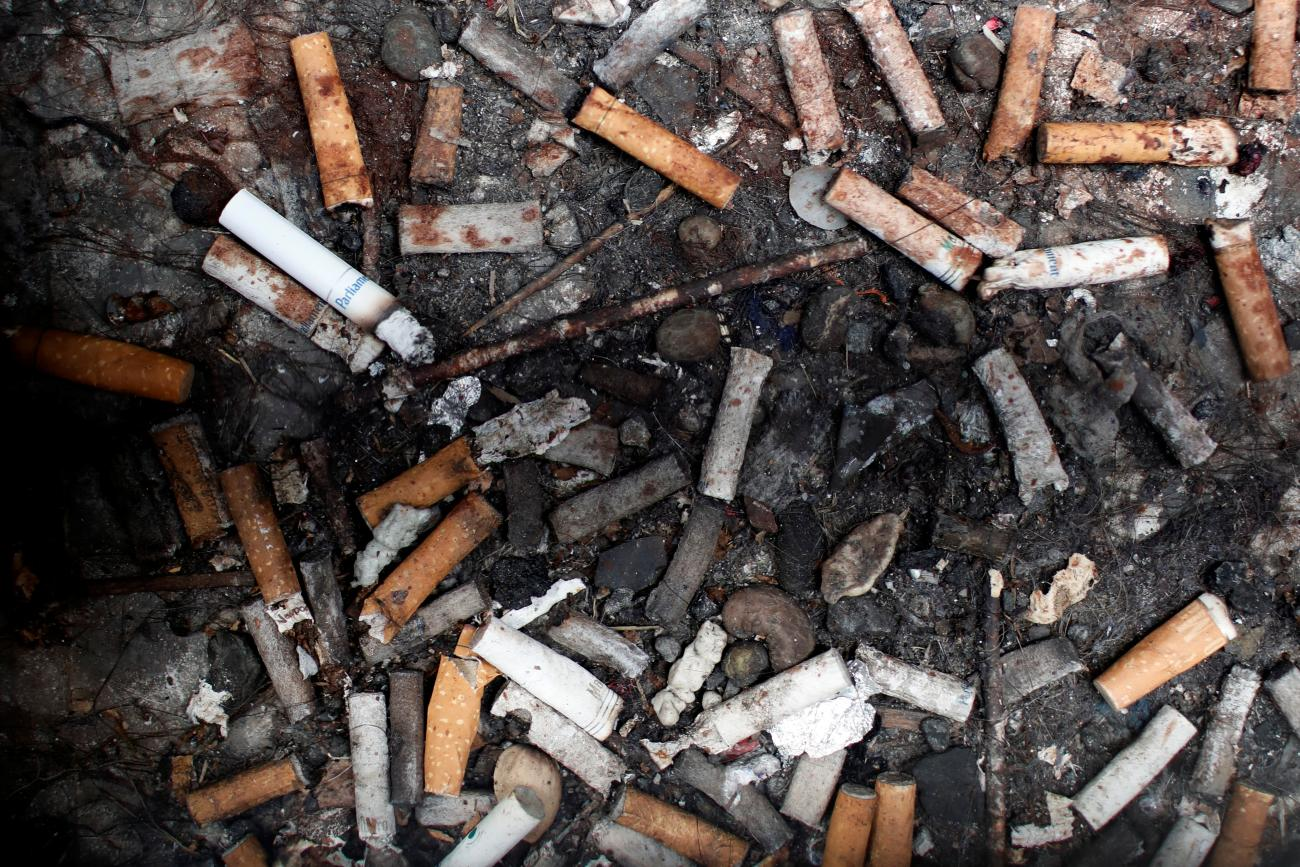 Discarded cigarette butts are seen beneath a sidewalk grating in Manhattan in New York City, May 8, 2017.