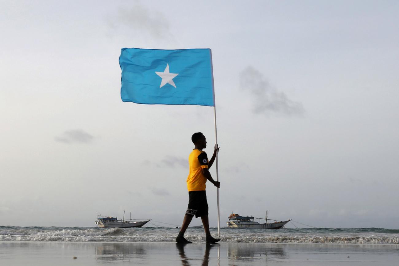 A young man holds Somalia's national flag, at Lido beach in Mogadishu, Somalia on June 18, 2021.