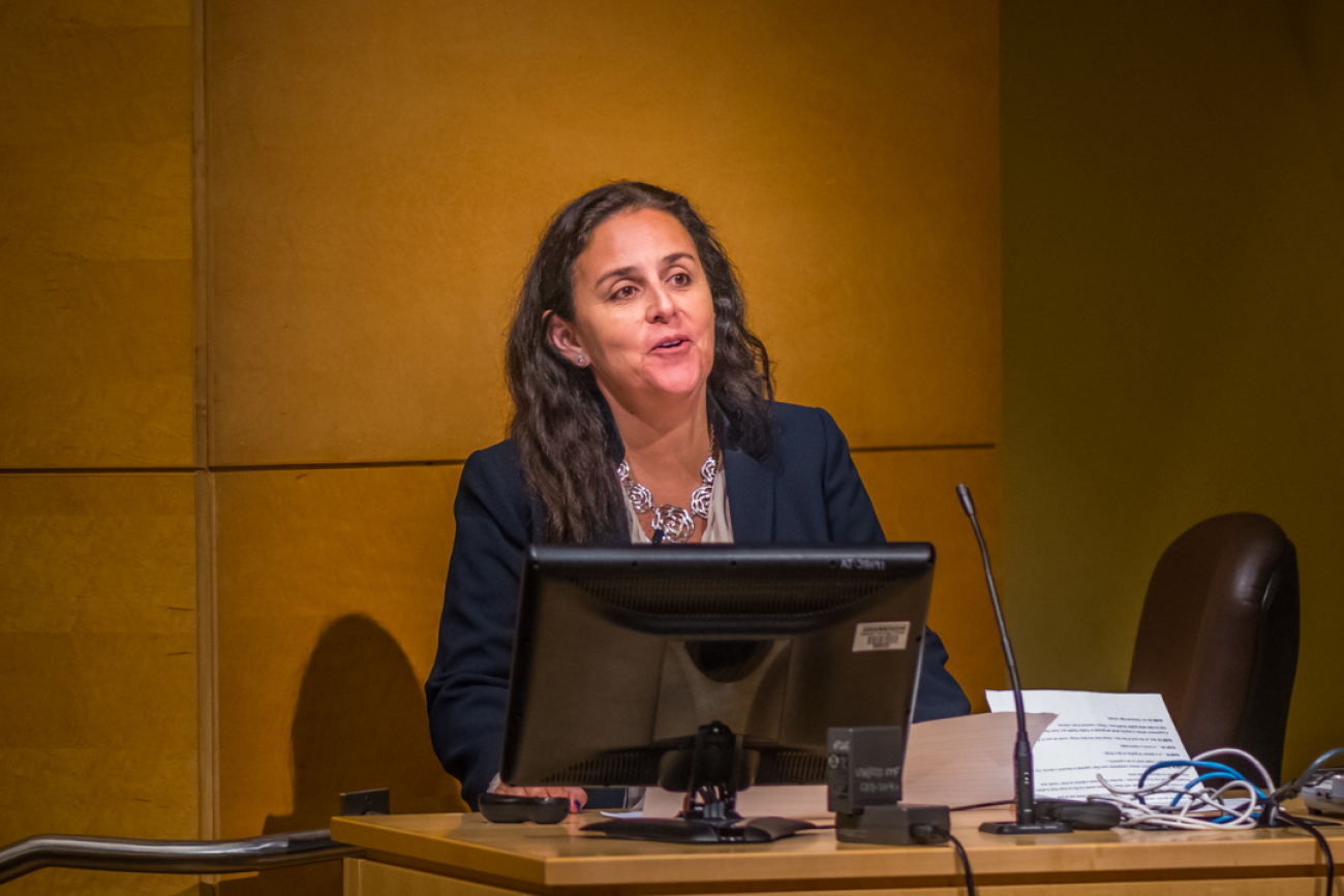 Dr. Patty García stands at a podium speaking. Dr. Garcia is professor and Dean of the School of Public Health at Universidad Peruana Cayetano Heredia in Lima, Peru. She is the former Minister of Health of Peru