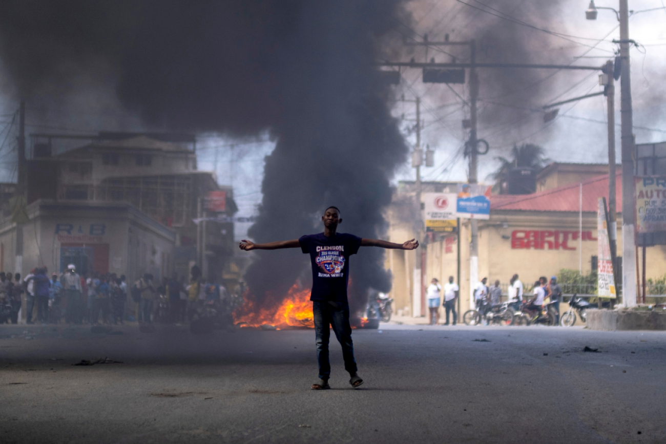 A man stands in front of a burning barricade during a protest against the assassination of Haitian President Jovenel Moise in Cap-Haitien, Haiti on July 22, 2021.