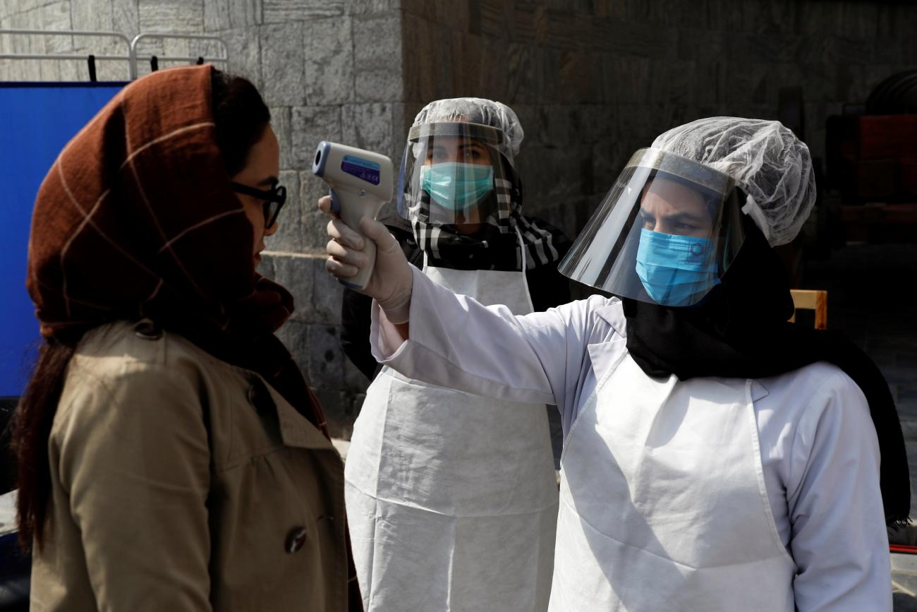 An Afghan health worker in protective gear checks the temperature of a woman before Afghanistan's President Ashraf Ghani inauguration as president, at the Presidential Palace in Kabul, Afghanistan March 9, 2020.