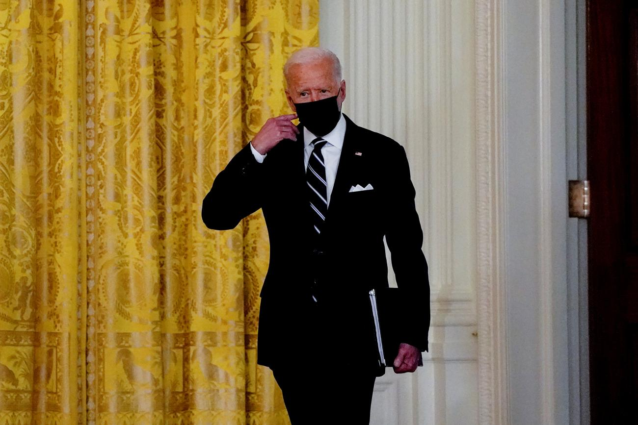 U.S. President Joe Biden removes his face mask as he arrives to deliver remarks on the COVID response and vaccination program at the White House in Washington, DC, on August 18, 2021.