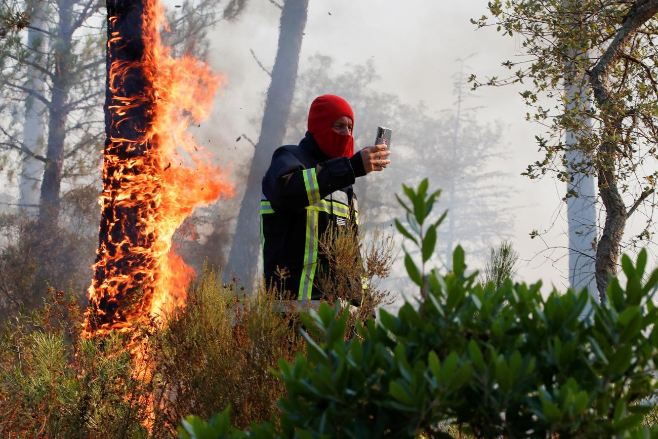 A firefighter takes a picture of a fire during a major wildfire that broke out in Vidauban, in the Var region of southern France, on August 18, 2021