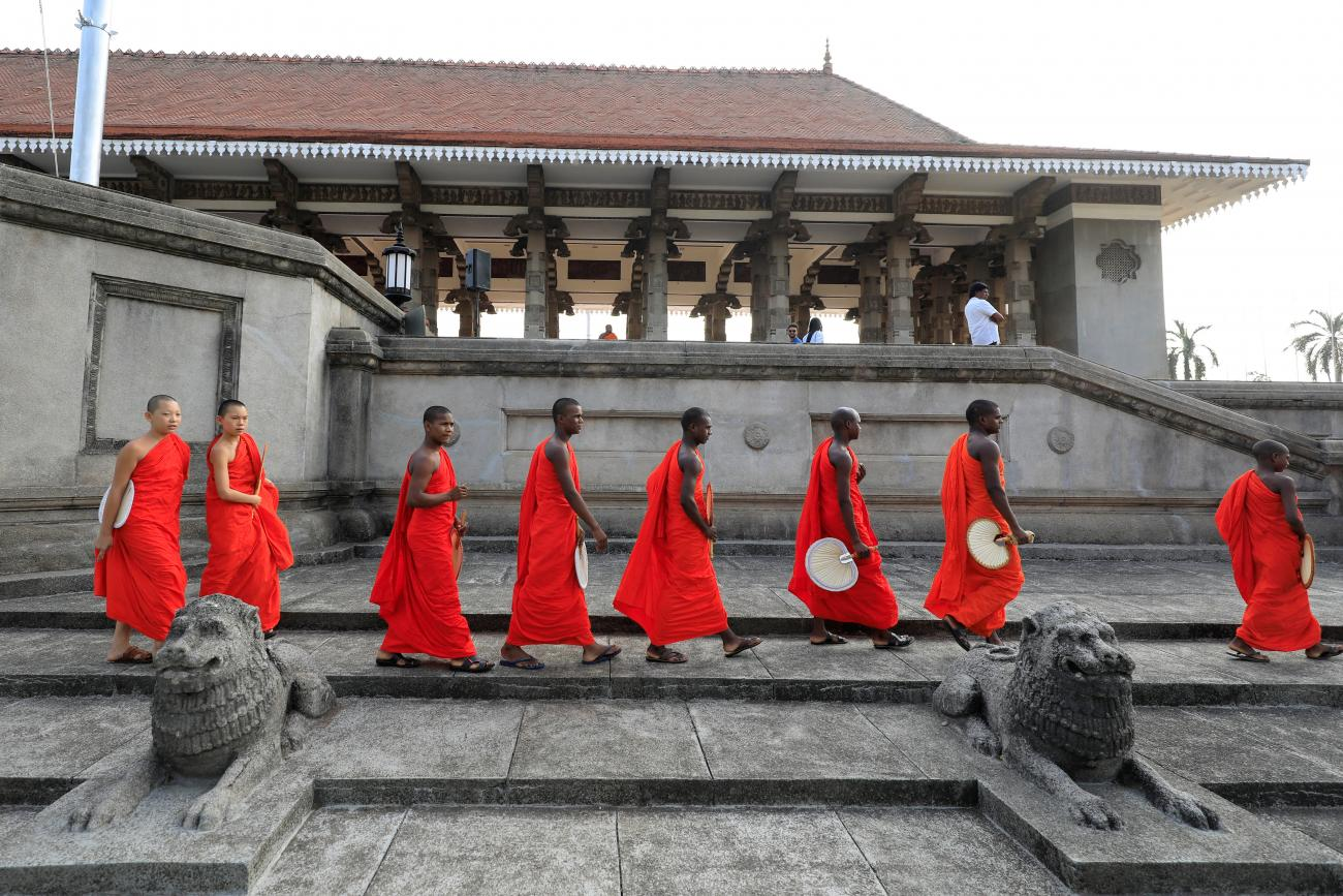 Monks dressed in red cross a temple