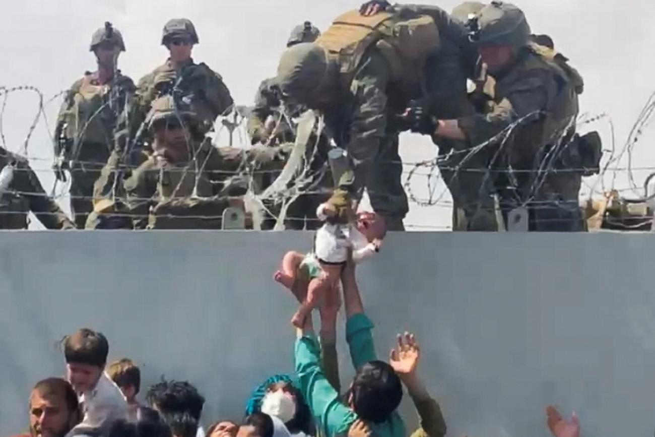 A baby is handed up to the U.S. Army over a perimeter wall at the airport in Kabul, Afghanistan, August 19, 2021 as Afghan civilians and U.S. citizens evacuated the city.