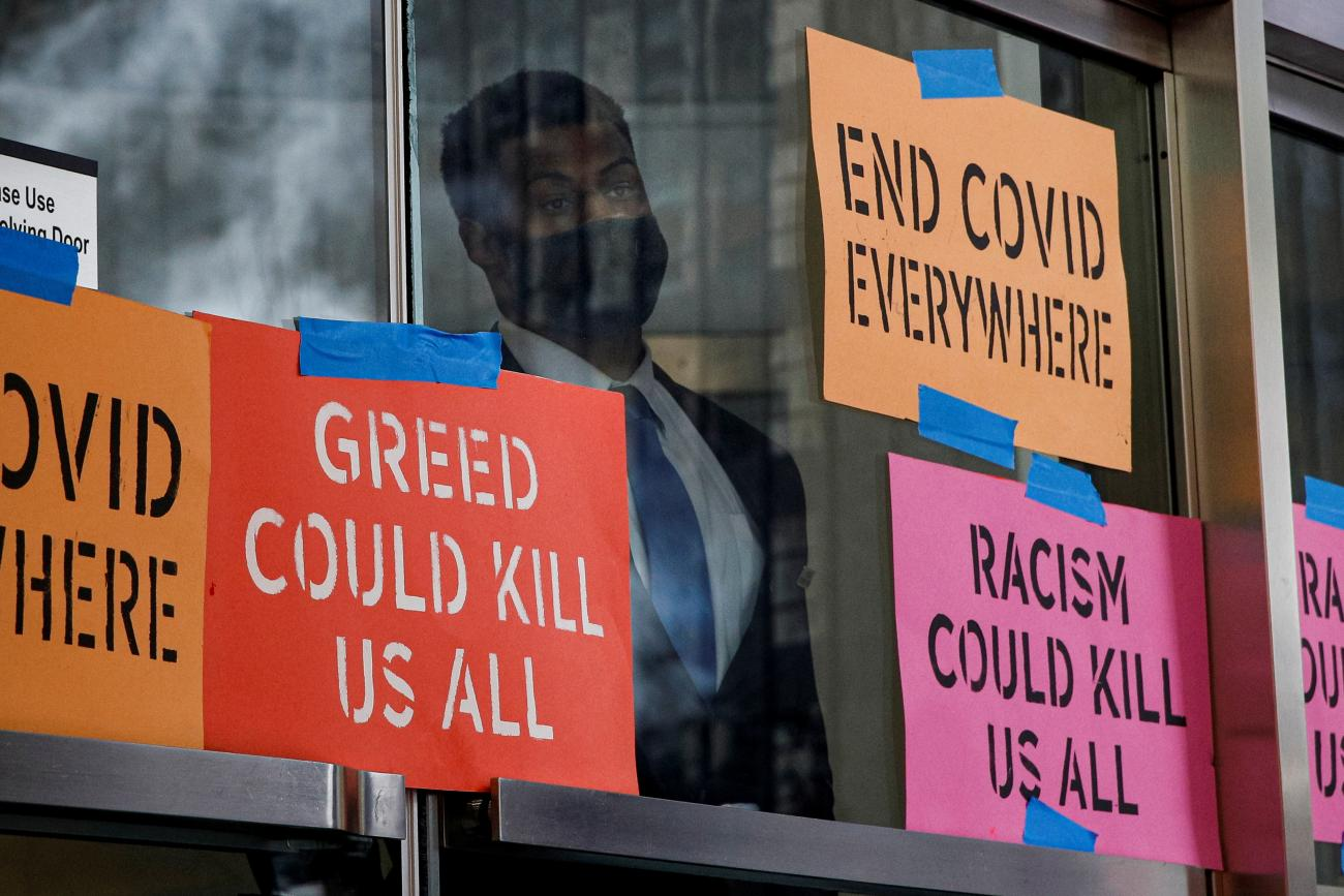 A security person looks out from the entrance to the Pfizer World Headquarters as activists rally for global access to the COVID-19 vaccine, in New York, July 14, 2021.