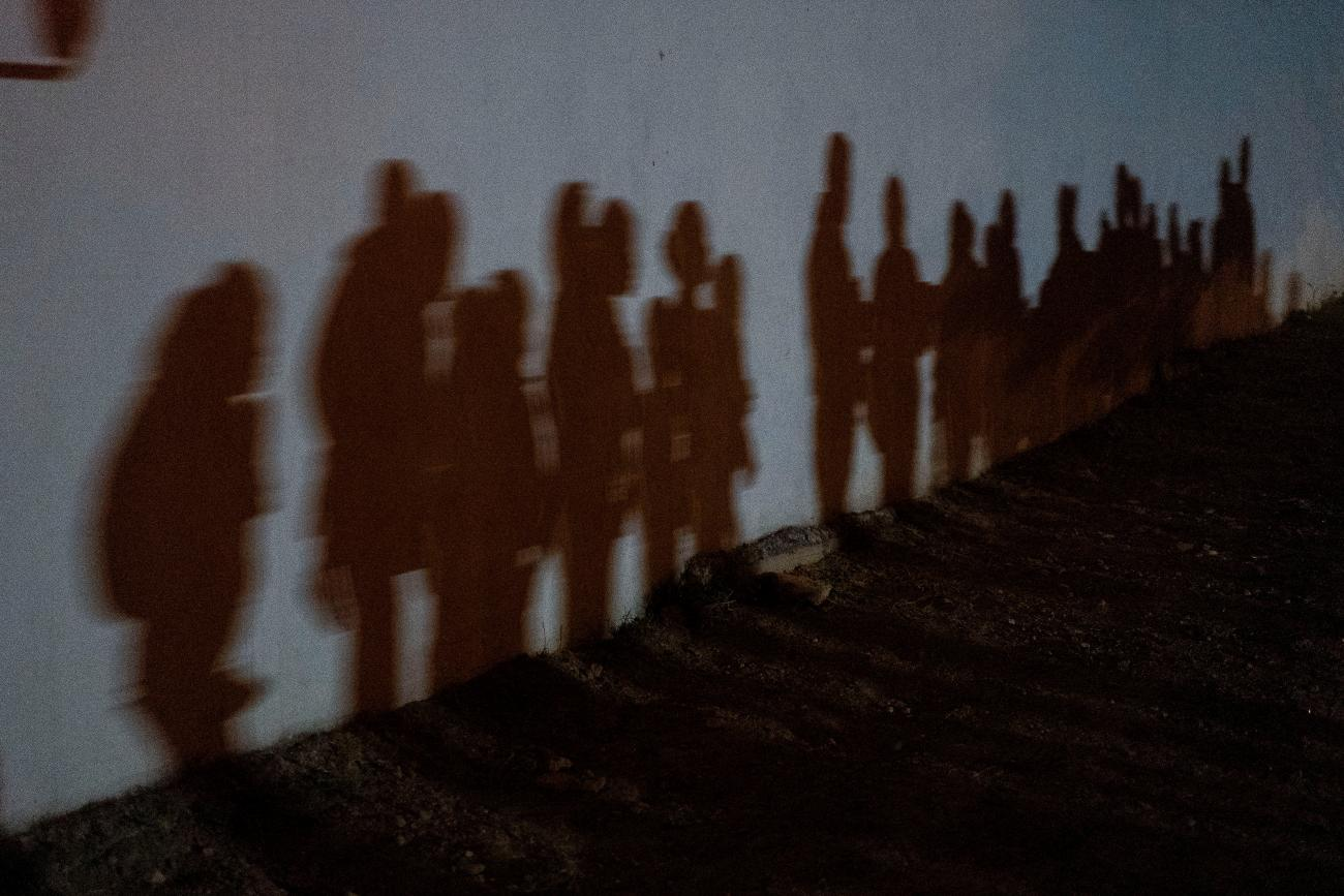 Shadows on a wall show asylum-seeking families as they queue up to be processed by the U.S. Border Patrol after crossing the Rio Grande River from Mexico, in Roma, Texas on August 12, 2021.