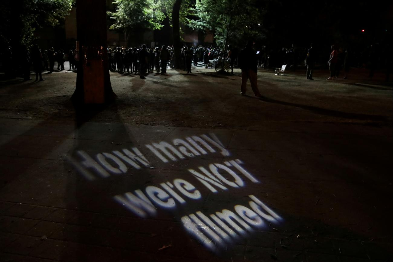 A protester casts a projection during a demonstration against police violence and racial inequality in Portland, Oregon, U.S., August 1, 2020.