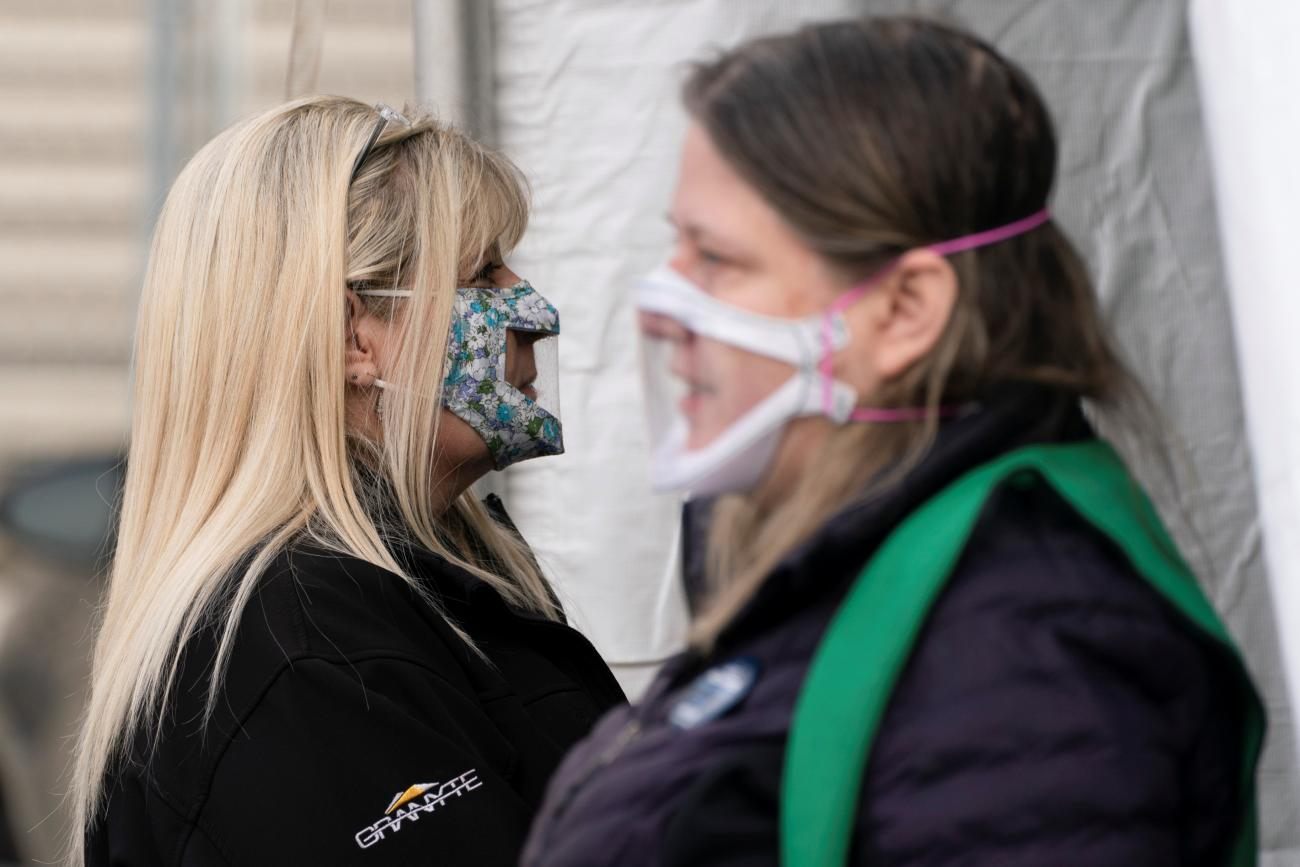 Interpreters wait at the entrance of a mobile coronavirus disease (COVID-19) vaccination clinic for members of the deaf and blind community, organized by the Swedish Medical Center in Seattle, Washington, U.S., March 19, 2021.