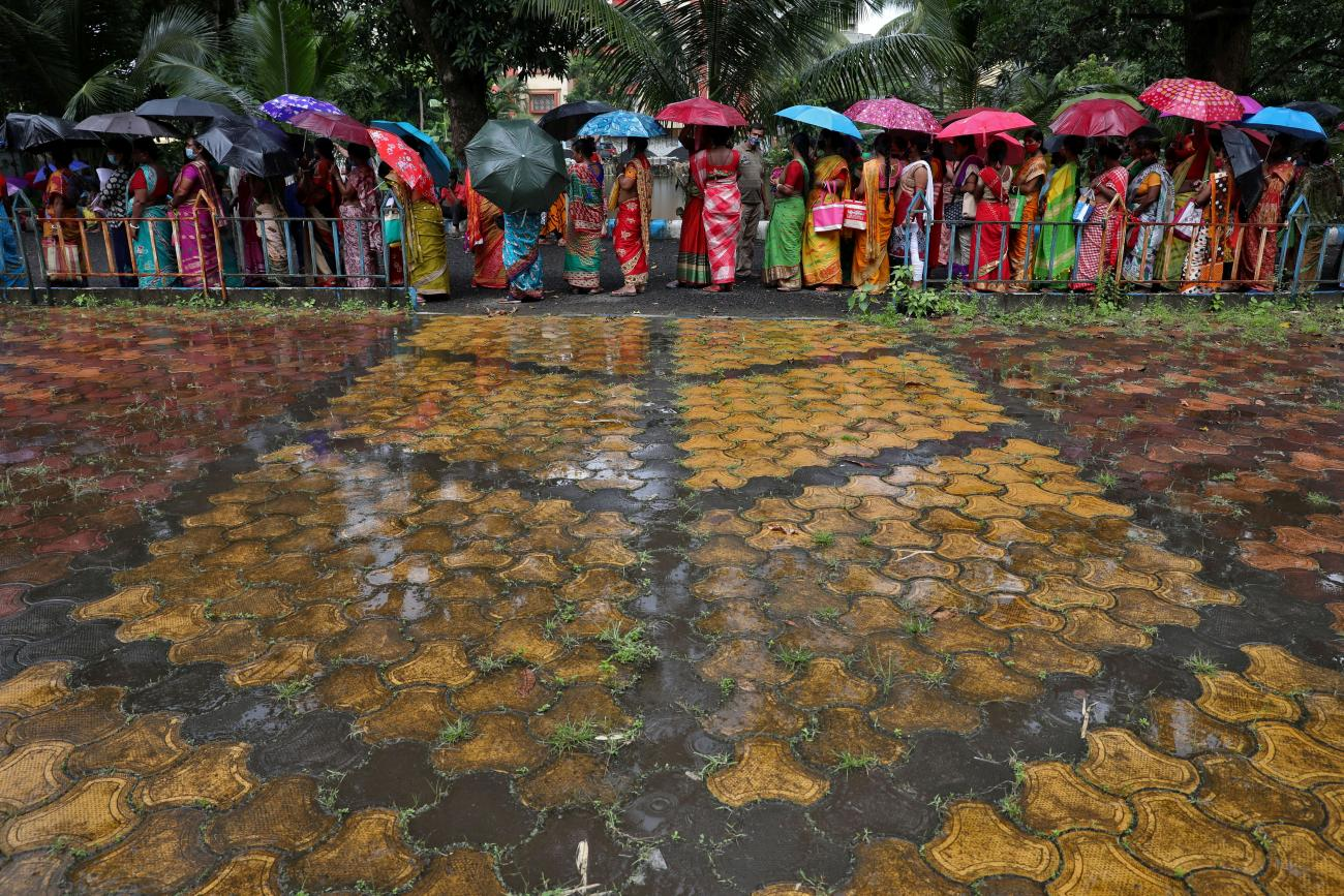 Women hold umbrellas to cover from rain as they wait to receive a dose of COVISHIELD vaccine, a COVID-19 vaccine made by Serum Institute of India, at a vaccination centre in Kolkata, India, August 31, 2021.
