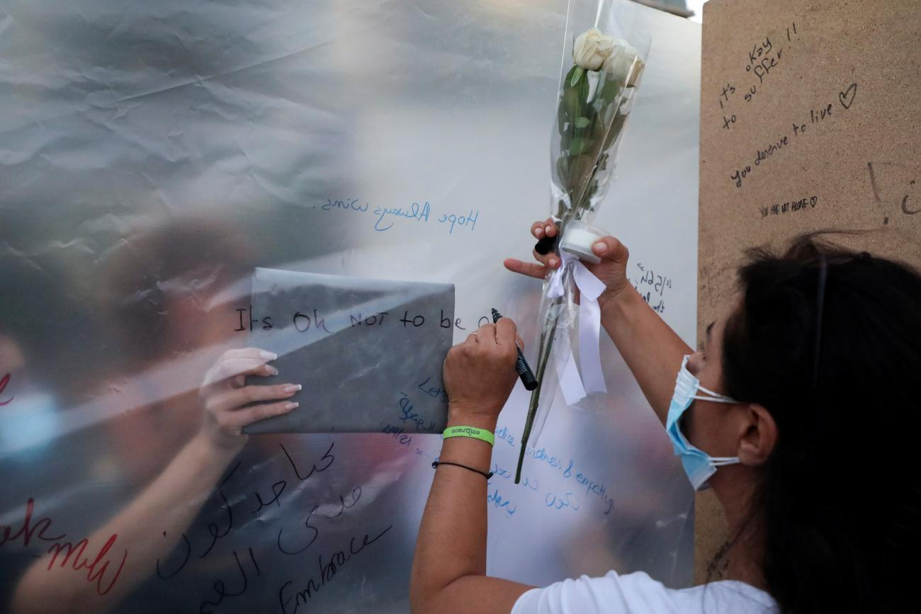 People write notes at the end point of a silent walk organized by Lebanese non-profit organization Embrace, marking World Suicide Prevention Day