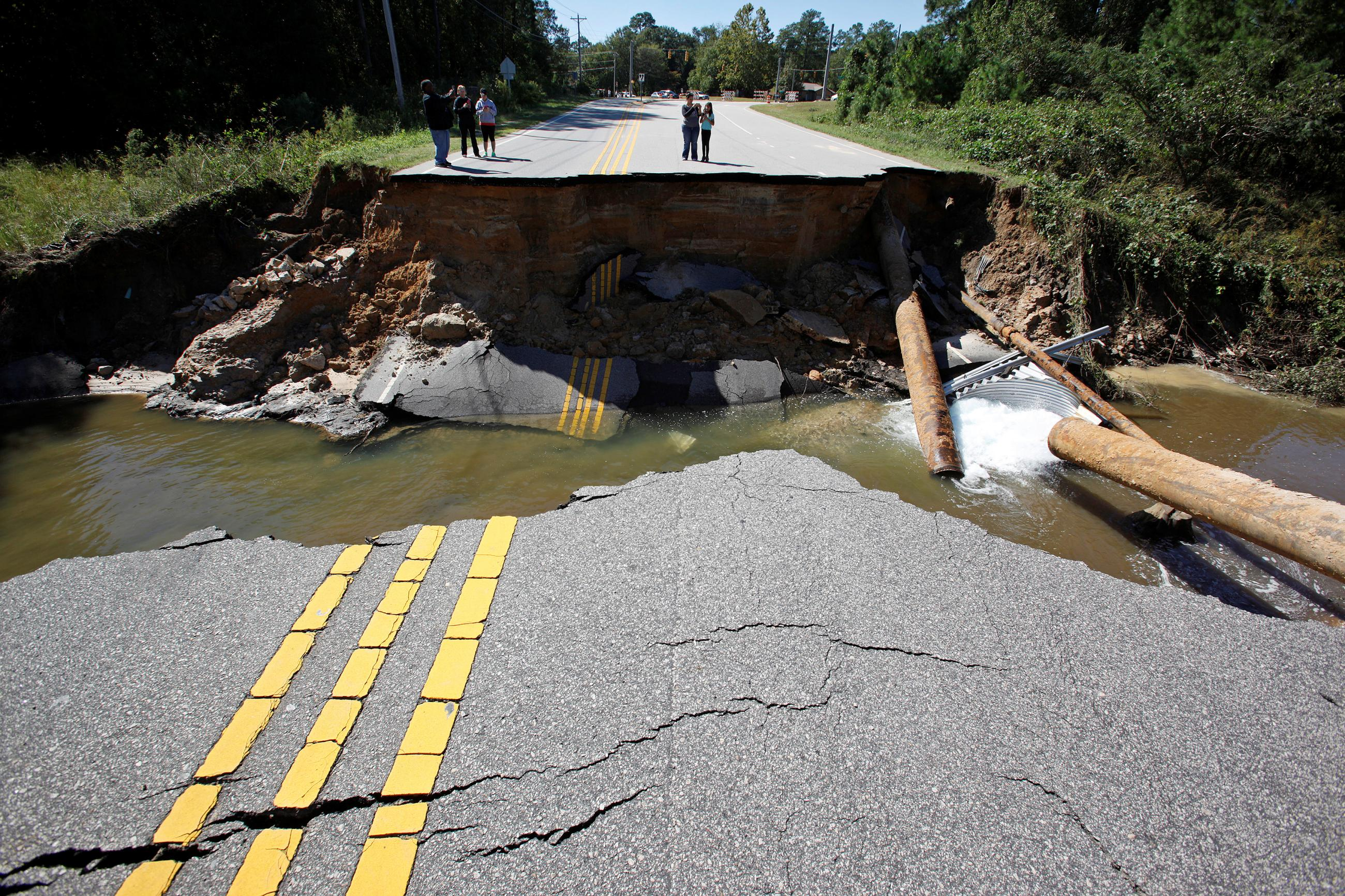 Residents inspect a washed-out section of collapsed road after Hurricane Matthew hit the state, in North Carolina.
