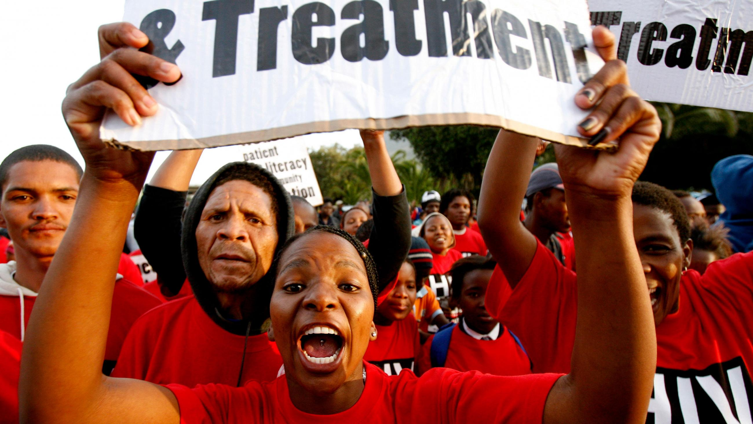 Demonstrators march through the streets of Cape Town to highlight the need for new strategies and medicines to curb the spread of tuberculosis on November 8, 2007. Picture shows a crowd of people wearing red shirts with a woman at center shouting into the camera