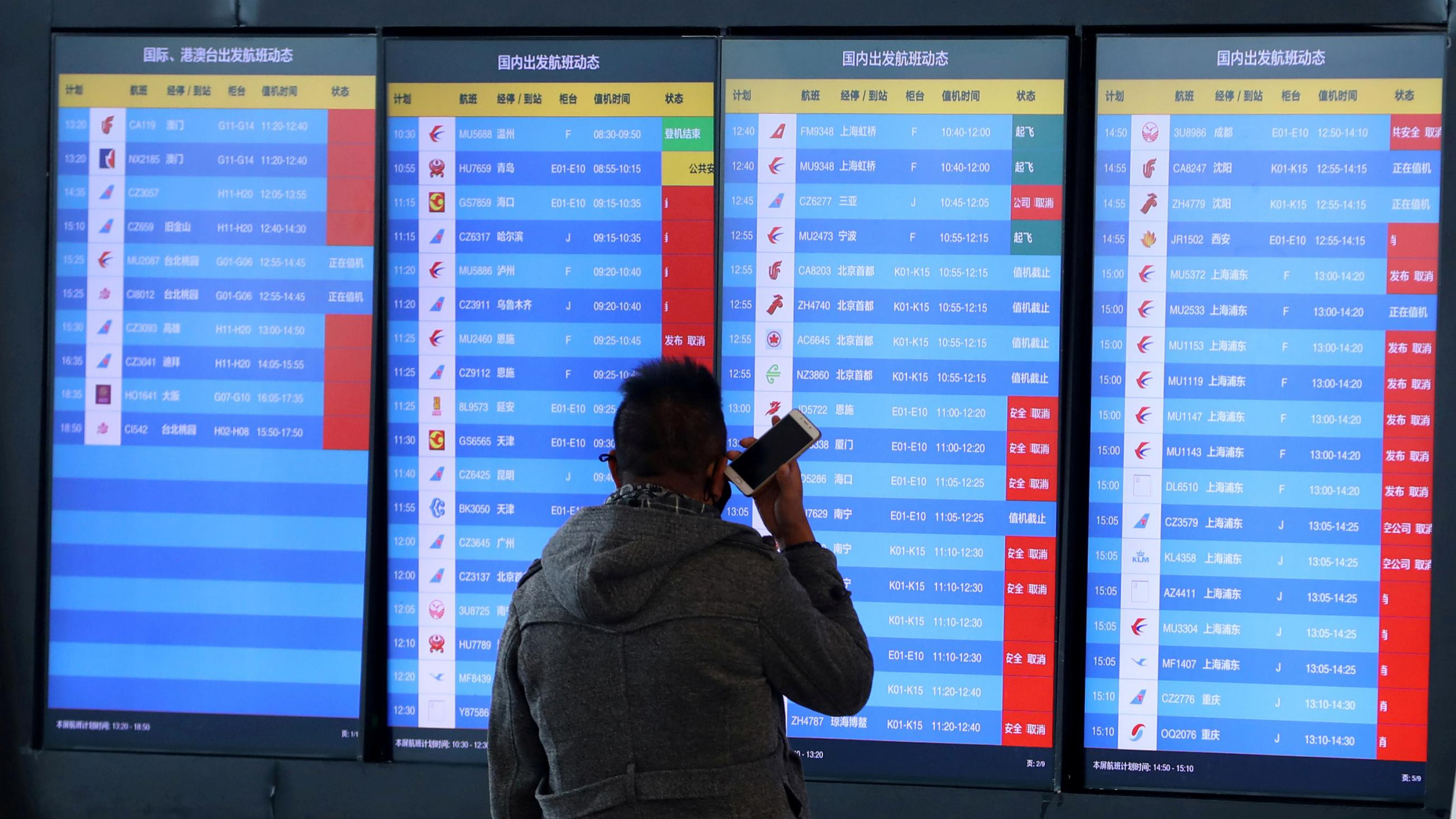 A man stands in front of an airport screen showing multiple flight departure cancellations after the city was locked down following the outbreak of a new coronavirus in Wuhan, China on Jan 23, 2020.