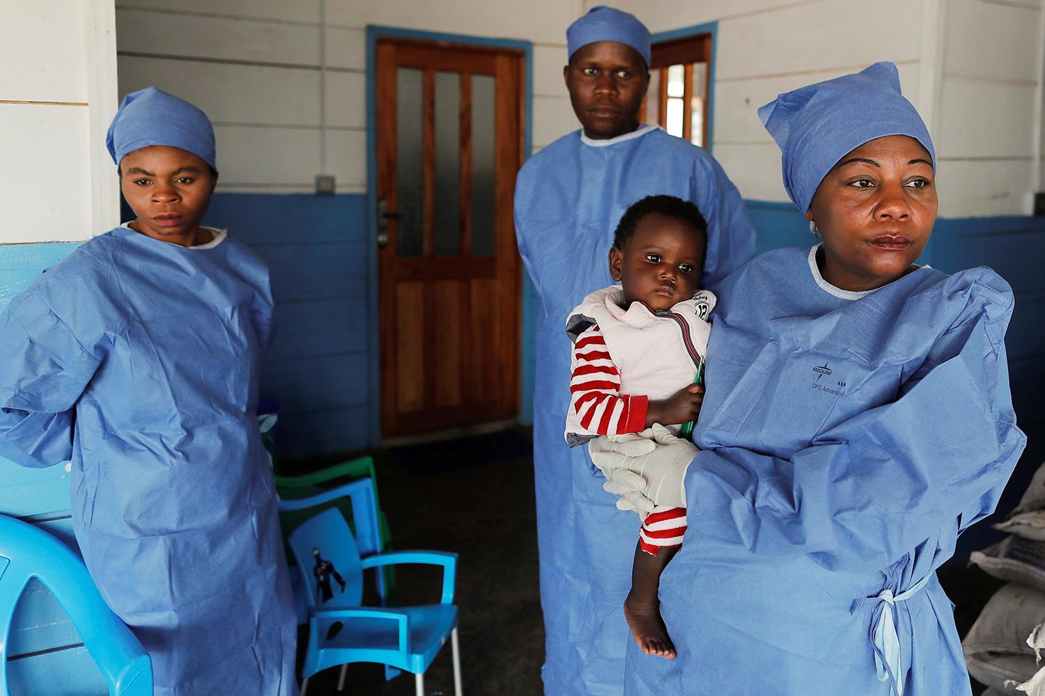 Arlette Kavugho, 40, a mother of six who survived an Ebola infection stands in Katwa, Democratic Republic of Congo, on October 2, 2019 holding 16 months old Kambale Eloge, whose mother died of Ebola. Photo shows Arlette holding the baby in front of a clinic while two other health workers stand in the background. REUTERS/Zohra Bensemra