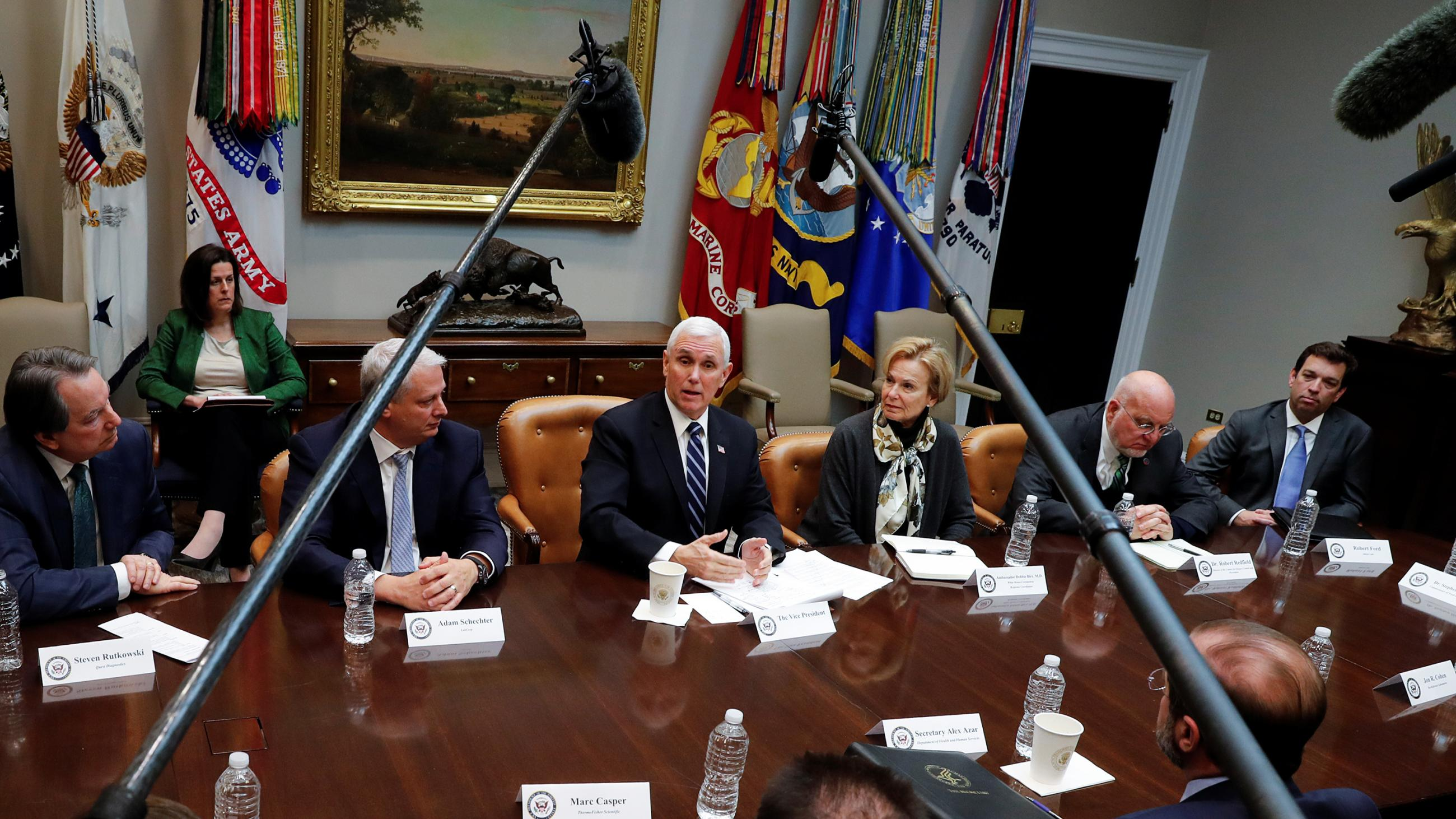 Photo shows the vice president at a large table speaking and surrounded by other people. Two microphone boom poles from opposite ends of the table extend out and converge over the table toward him.