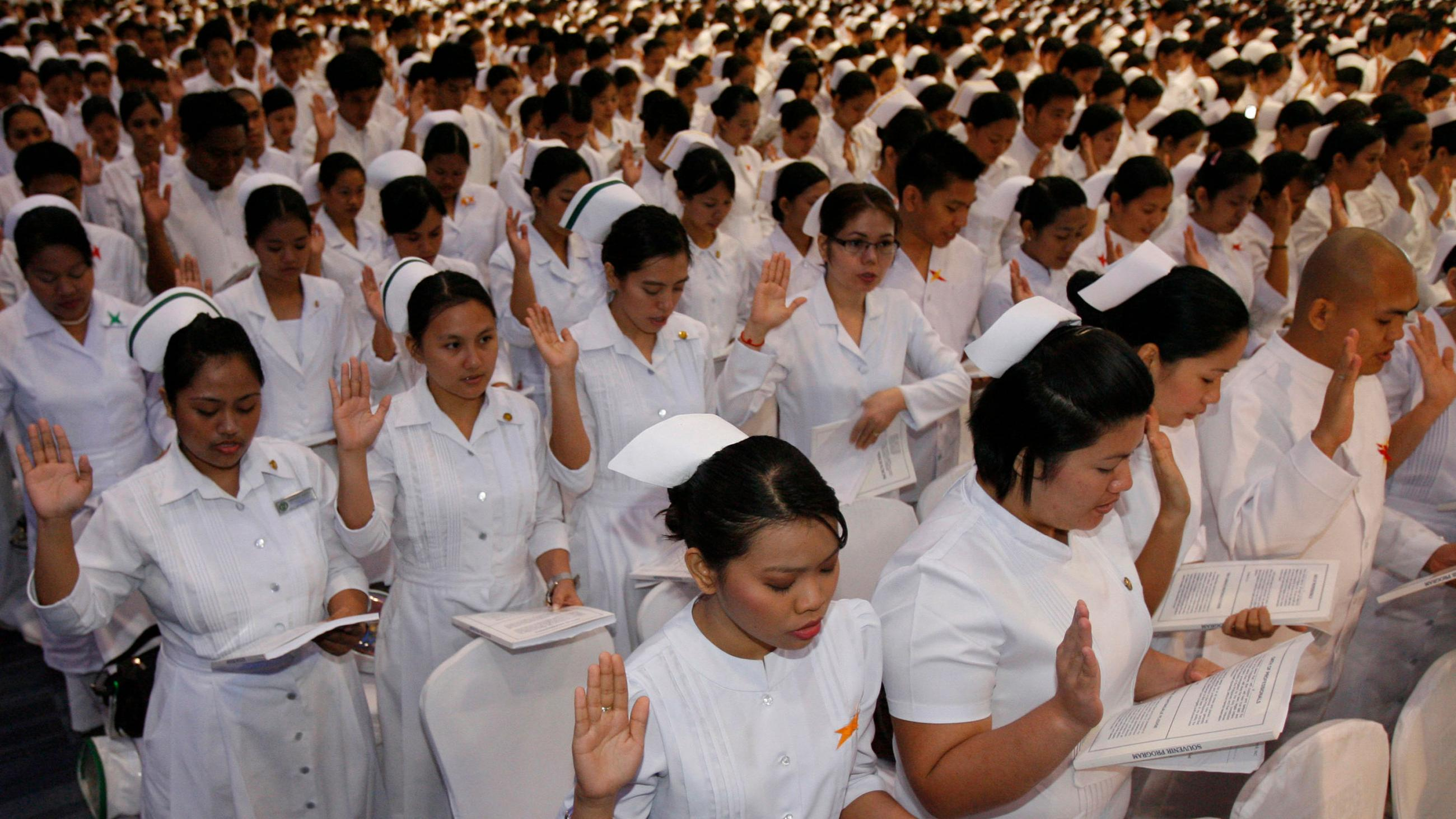 Picture shows thousands and thousands of nurses in uniform lined up with right hands raised reading from a thick packet. The women have traditional nurse caps, but the men's heads are bare.
