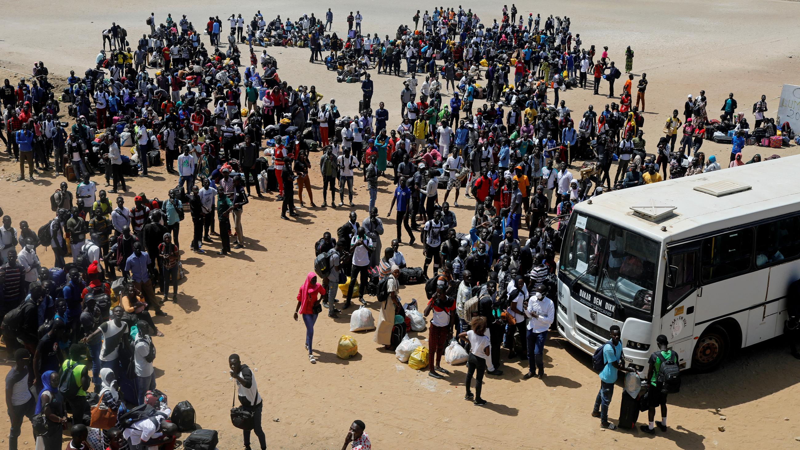 The image is a distance shot of a huge crowd of students with bags in an open area with a single lage bus parked.