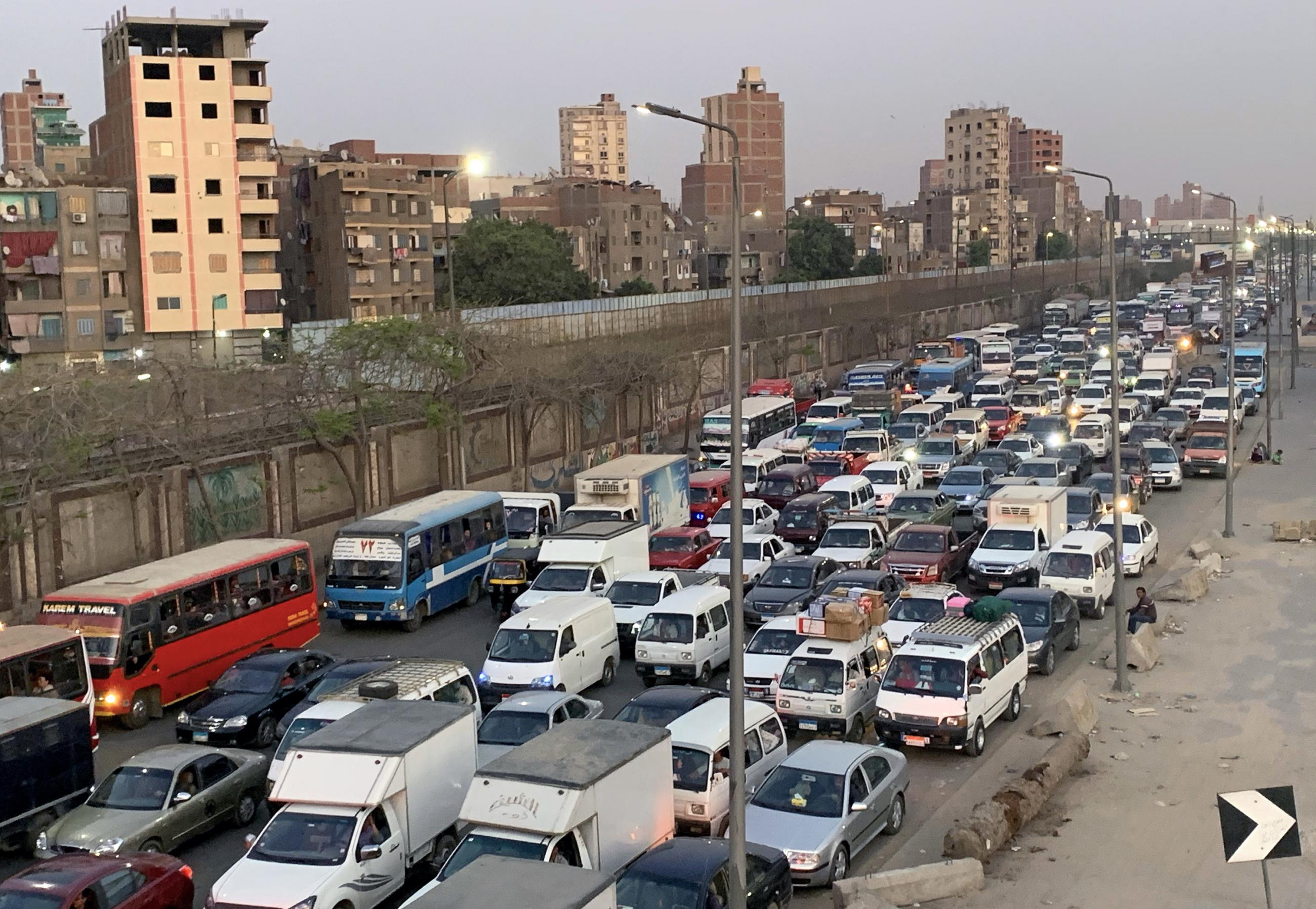 The photo shows a dusty street packed with cars and trucks.