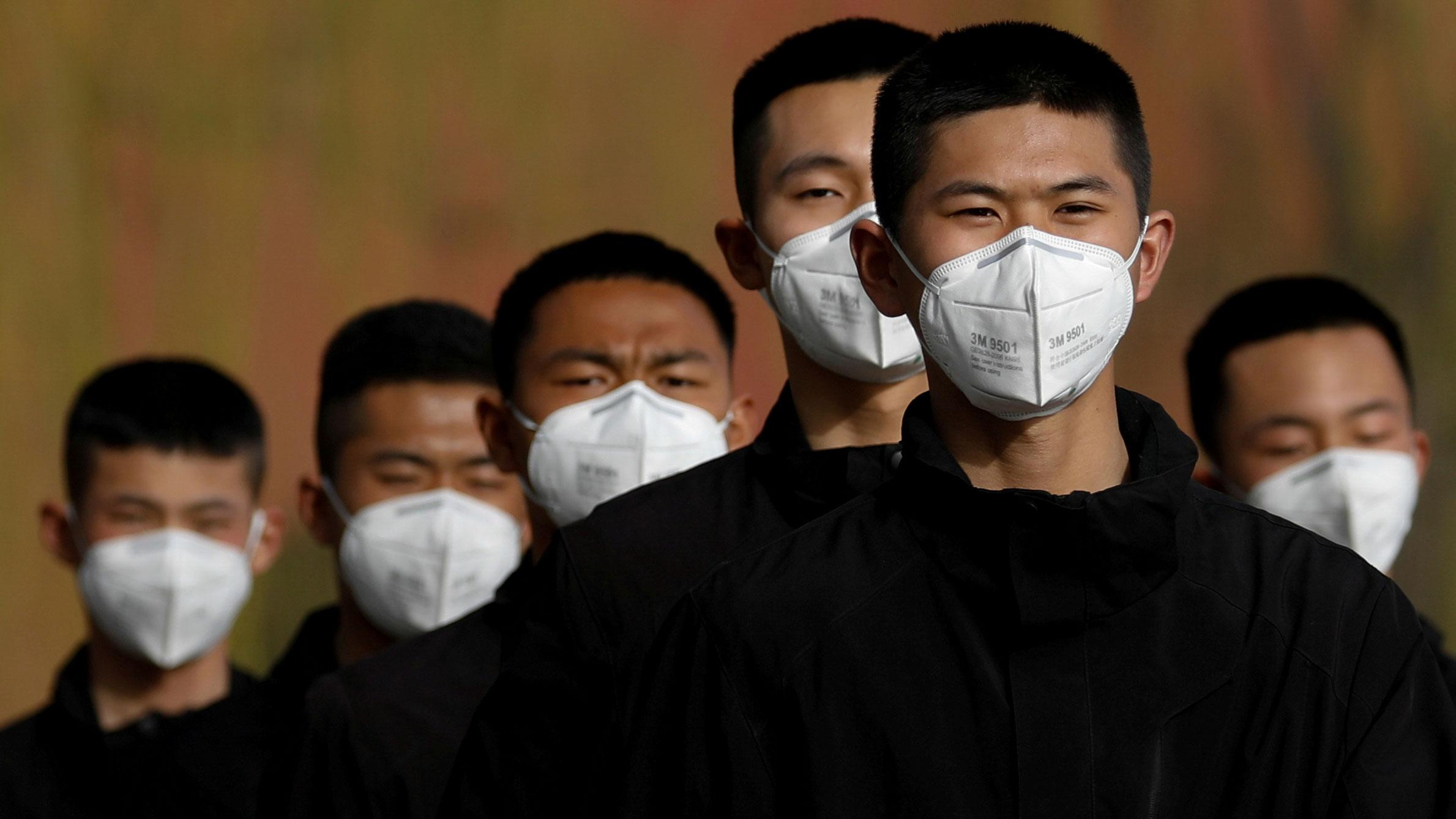 The photo shows half a dozen young men with short cropped hair and all-black clothes in a line, wearing masks.