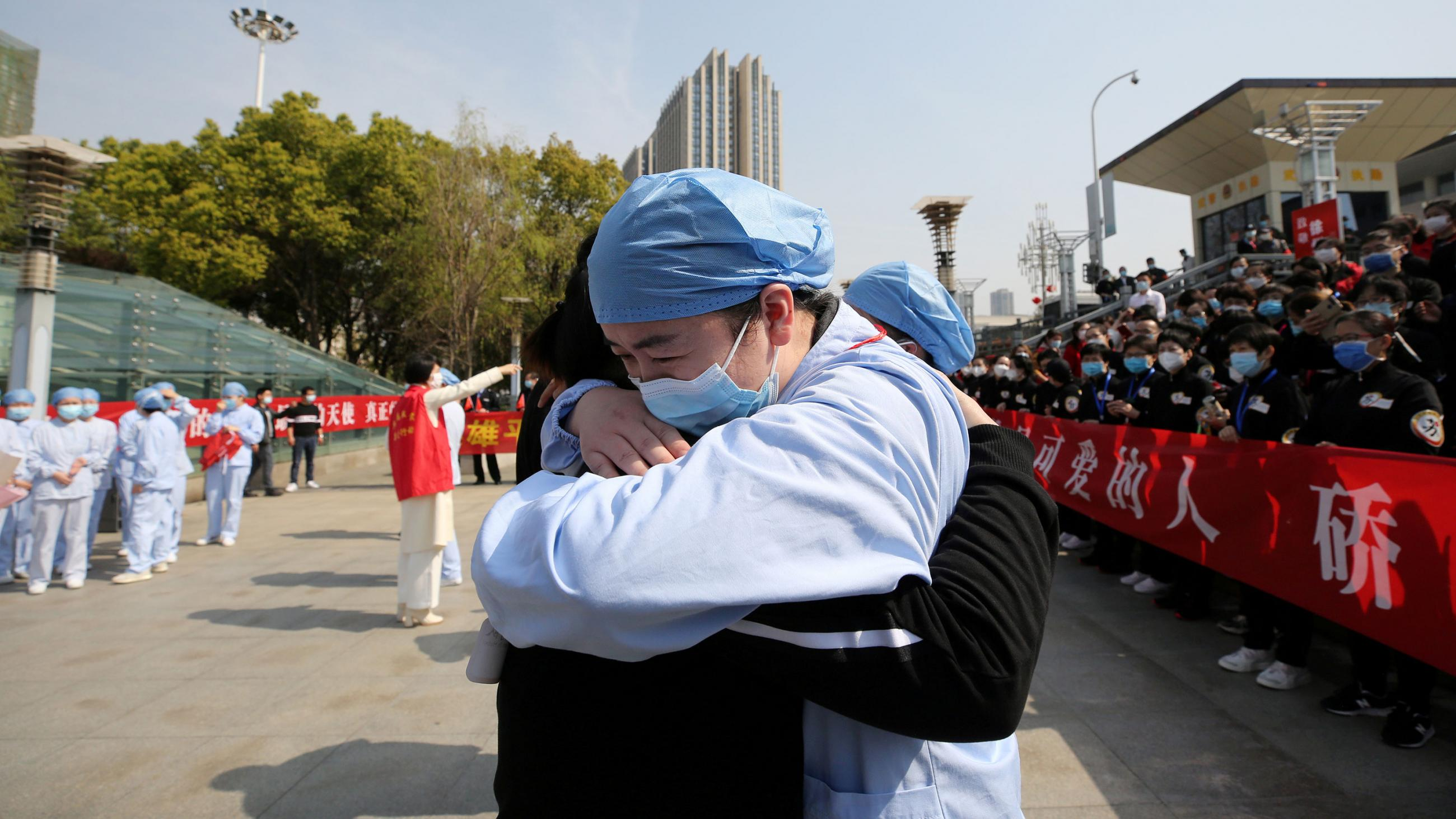 The photo shows two medical workers hugging in what is obviously an emotional scene.