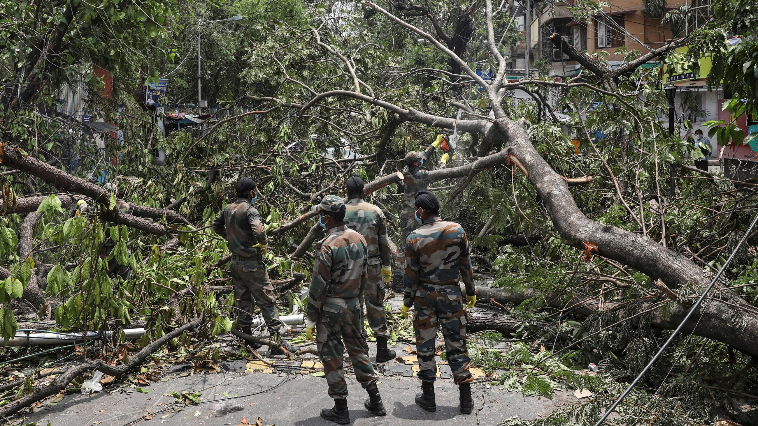 The photo shows several soldiers standing amid fallen trees and other storm-related destruction.