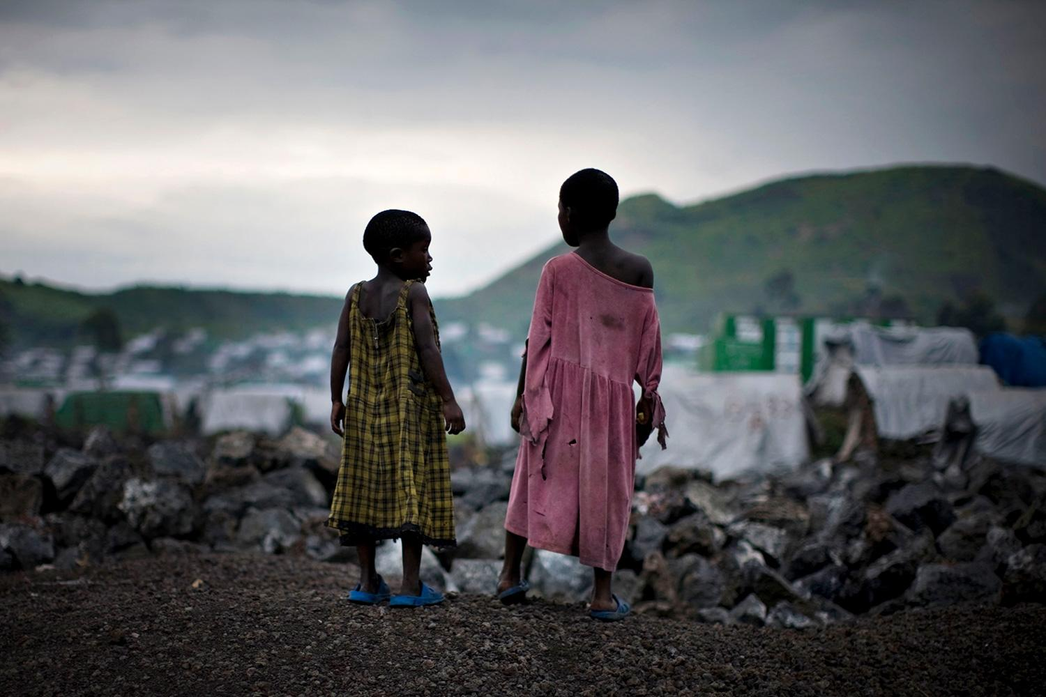 Congolese girls displaced by war stand on the outskirts of a makeshift camp near Goma in eastern Democratic Republic of Congo on February 11, 2009. The photo shows two girls standing on a hill overlooking a camp filled with white tents at sunset. REUTERS/Finbarr O'Reilly