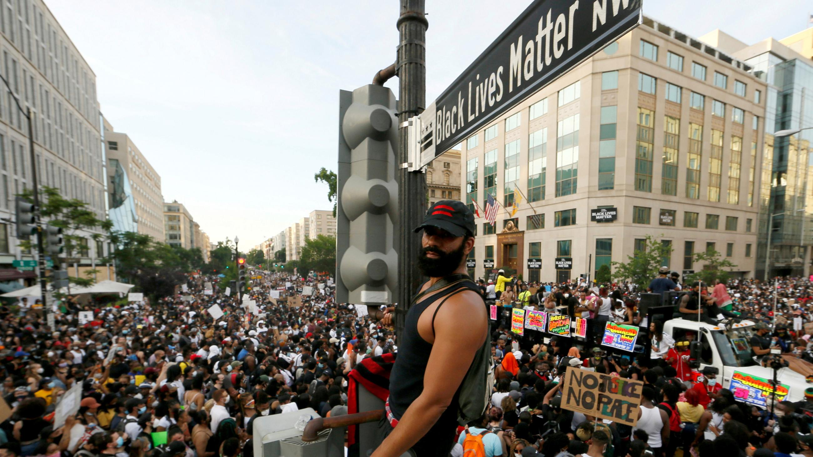 The photo shows the protestor standing on the light post above a massive crowd.