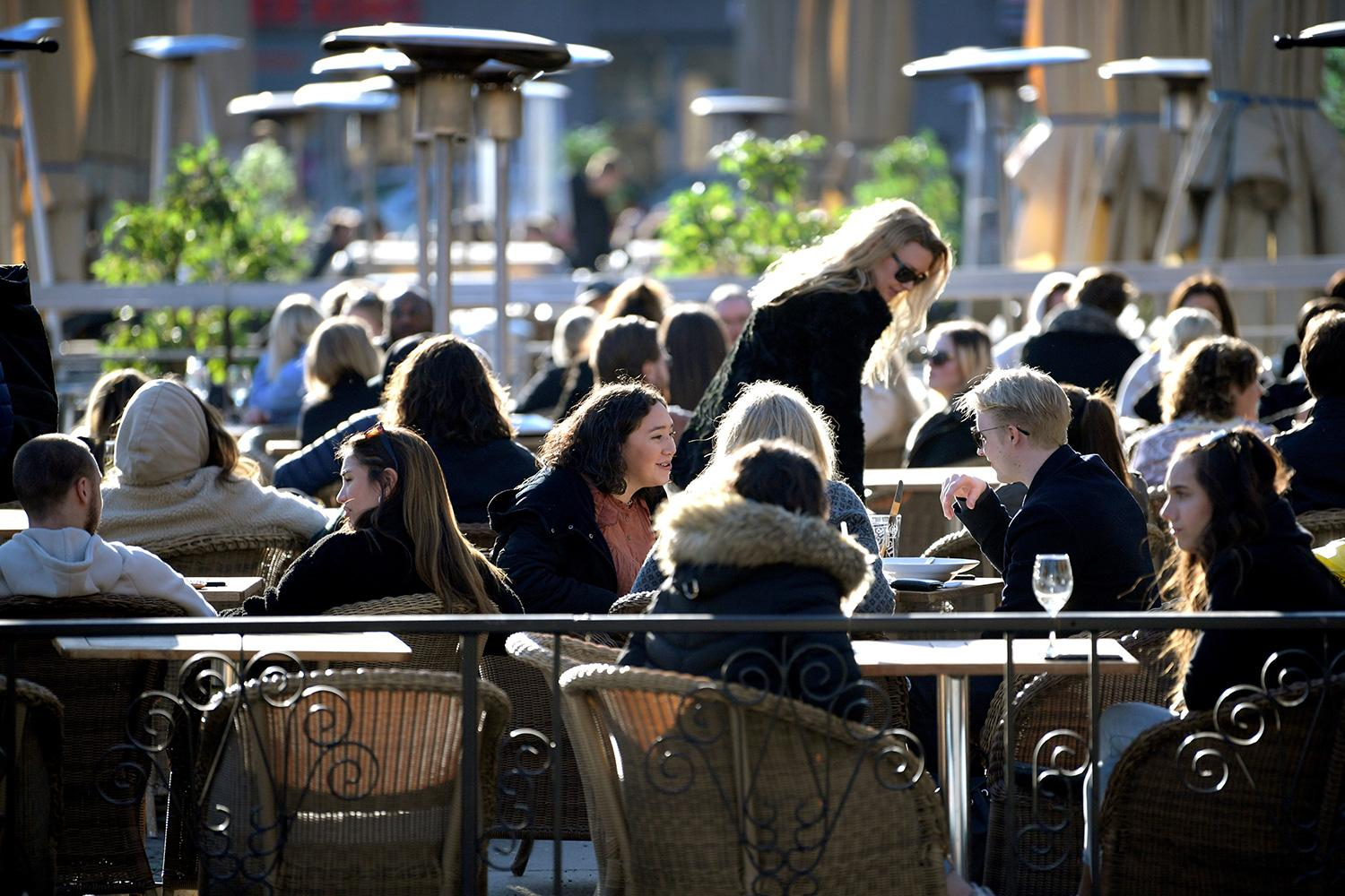 People enjoy the sun at an outdoor restaurant, despite the continuing spread of the coronavirus disease (COVID-19), in Stockholm, Sweden March 26, 2020. The photo shows a large number of people sitting lose together in an outdoor eating area. TT News Agency/Janerik Henriksson via REUTERS