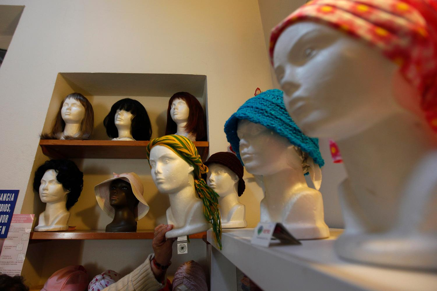 """Wigs and head scarves for patients with breast cancer are seen on mannequins at a center run by the """"Reto"""" Group for Full Recovery of Breast Cancer in Mexico City October 18, 2012. The photo shows a room with mannequin heads and wigs. REUTERS/Edgard Garrido"""