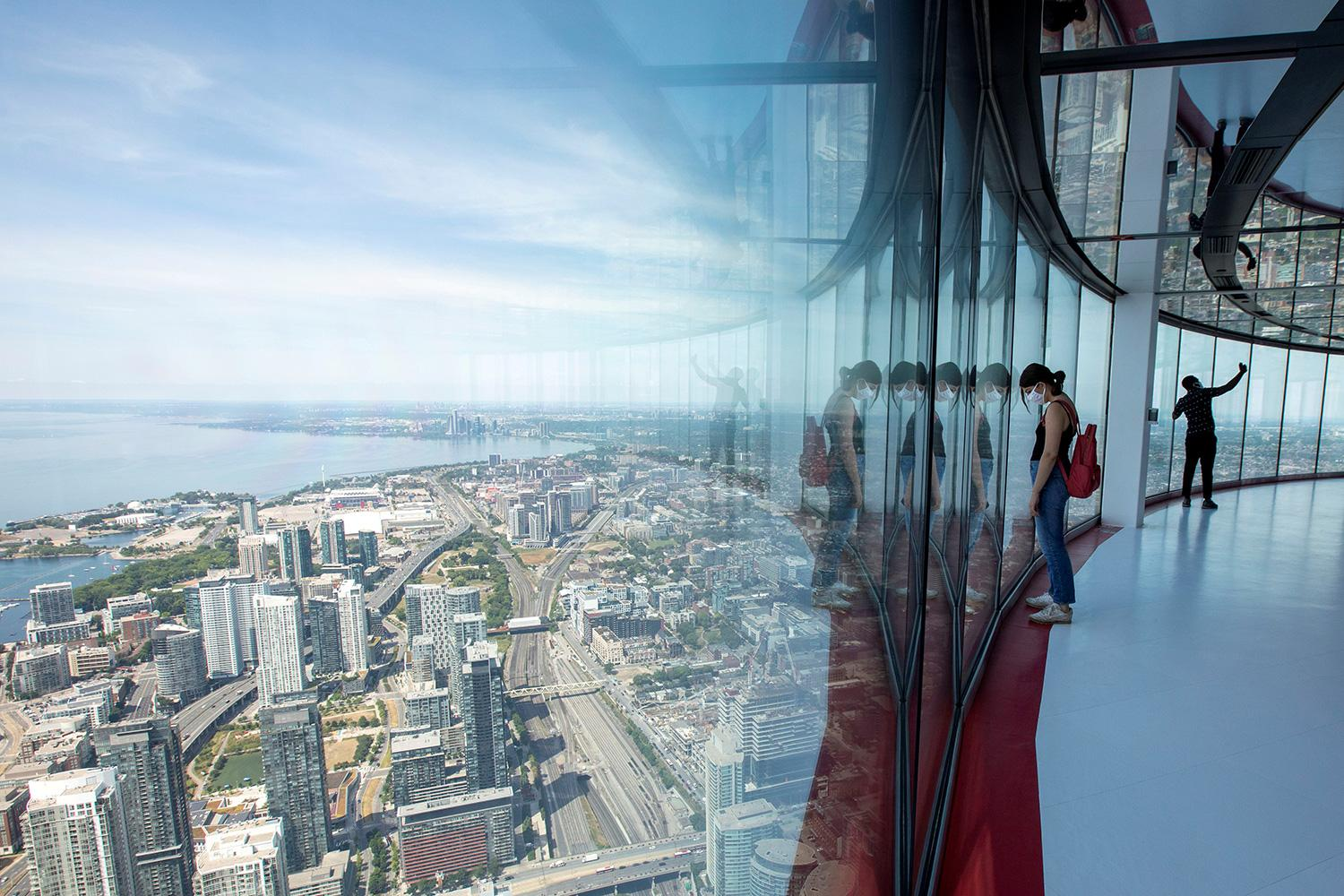 Bird's eye view: visitors take in a panoramic scene of the city of Toronto, Canada, from the 553 meters (1815 feet) high CN Tower, which just reopened after coronavirus restrictions on July 15, 2020. The photo shows a woman wearing a mask looking out from the skyview of the tall building with the Toronto cityscape beneath her. REUTERS/Carlos Osorio