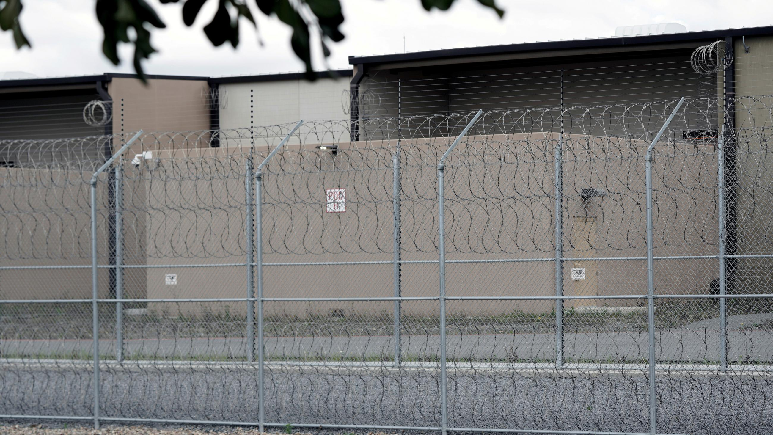 The photo shows a lockup from outside its perimeter barbed wire fence.