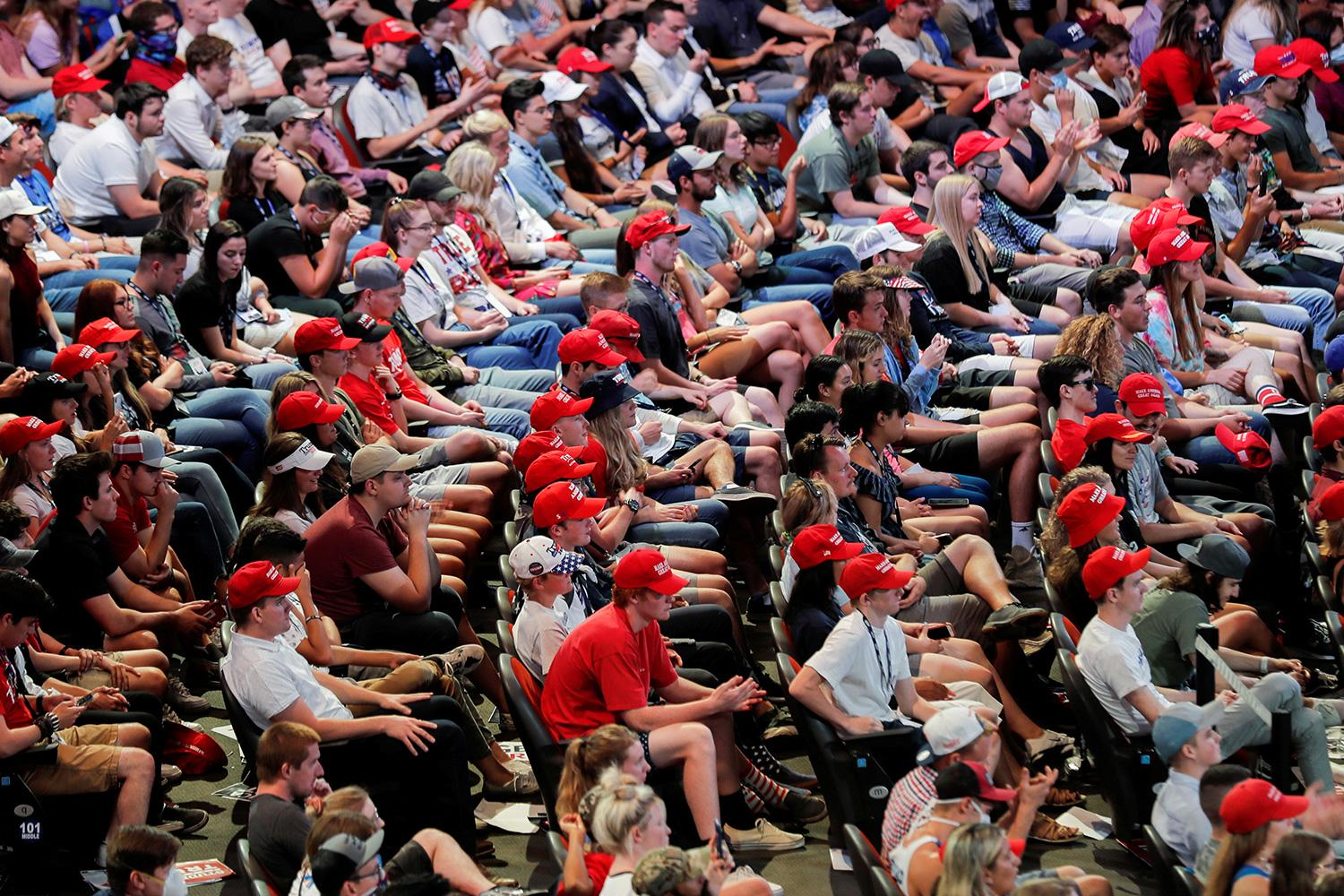 Ignoring the science on social distancing, not congregating indoors, and wearing masks, young people listen to U.S. President Donald J. Trump at the Dream City Church in Phoenix on June 23, 2020. The photo shows a huge crowd of yound people, very few wearing masks, packed into theater-like seats. REUTERS/Carlos Barria