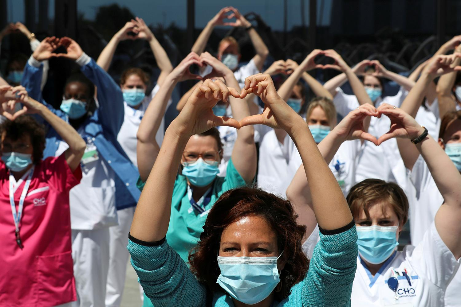 """Health-care workers, nurses, and doctors, protesting under the movement called """"Take Care of Care"""" during the coronavirus crisis, at the MontLegia CHC Hospital in Liege, Belgium, on May 15, 2020. The photo shows a large number of health workers standing together and holding up a heart symbol above their heads. REUTERS/Yves Herman"""