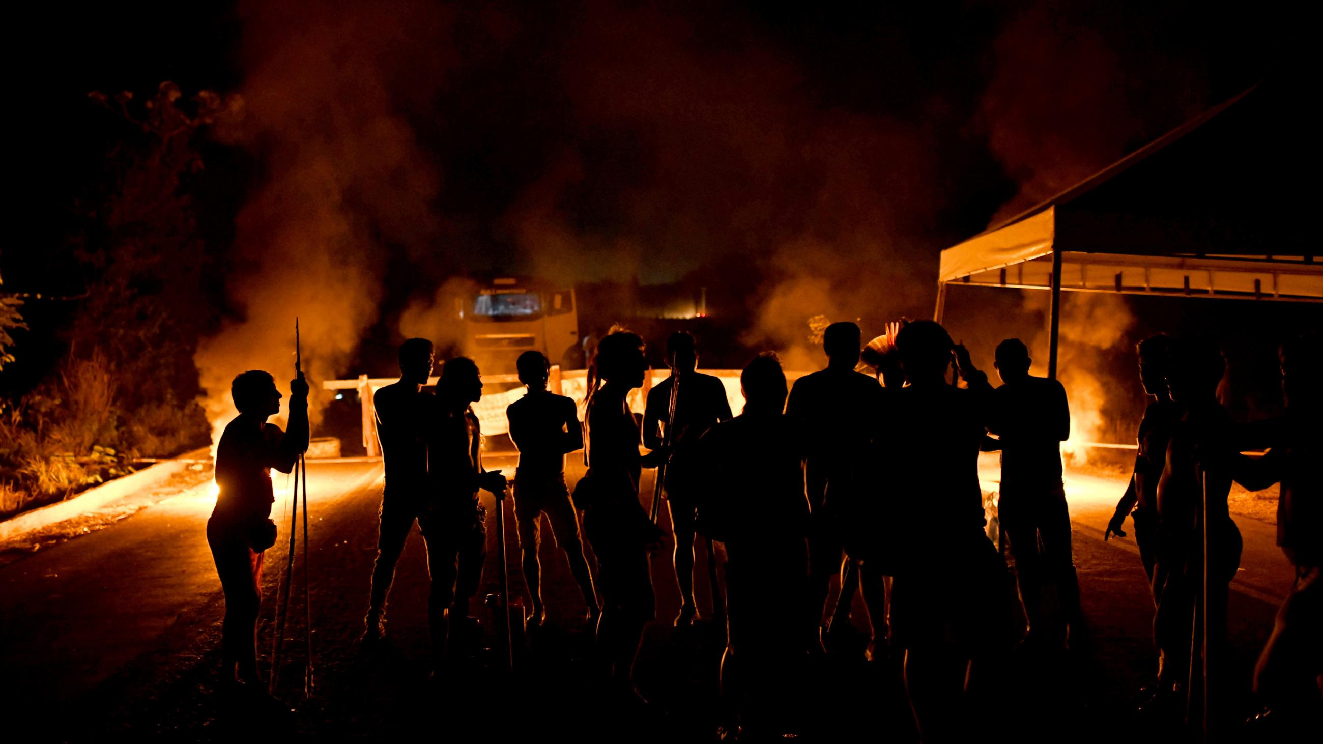 The image shows a large number of protesters at night silhouetted against a fire burning.