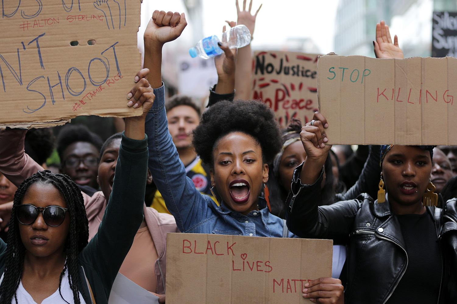 Demonstrators from the Black Lives Matter movement march through central London on July 10, 2016, during a demonstration against the killing of black men by police in the United States. The photo shows a huge crowd with people facing the camera with homemade signs, fists raised, and shouting slogans. AFP/Daniel Leal-Olivas via Getty Images
