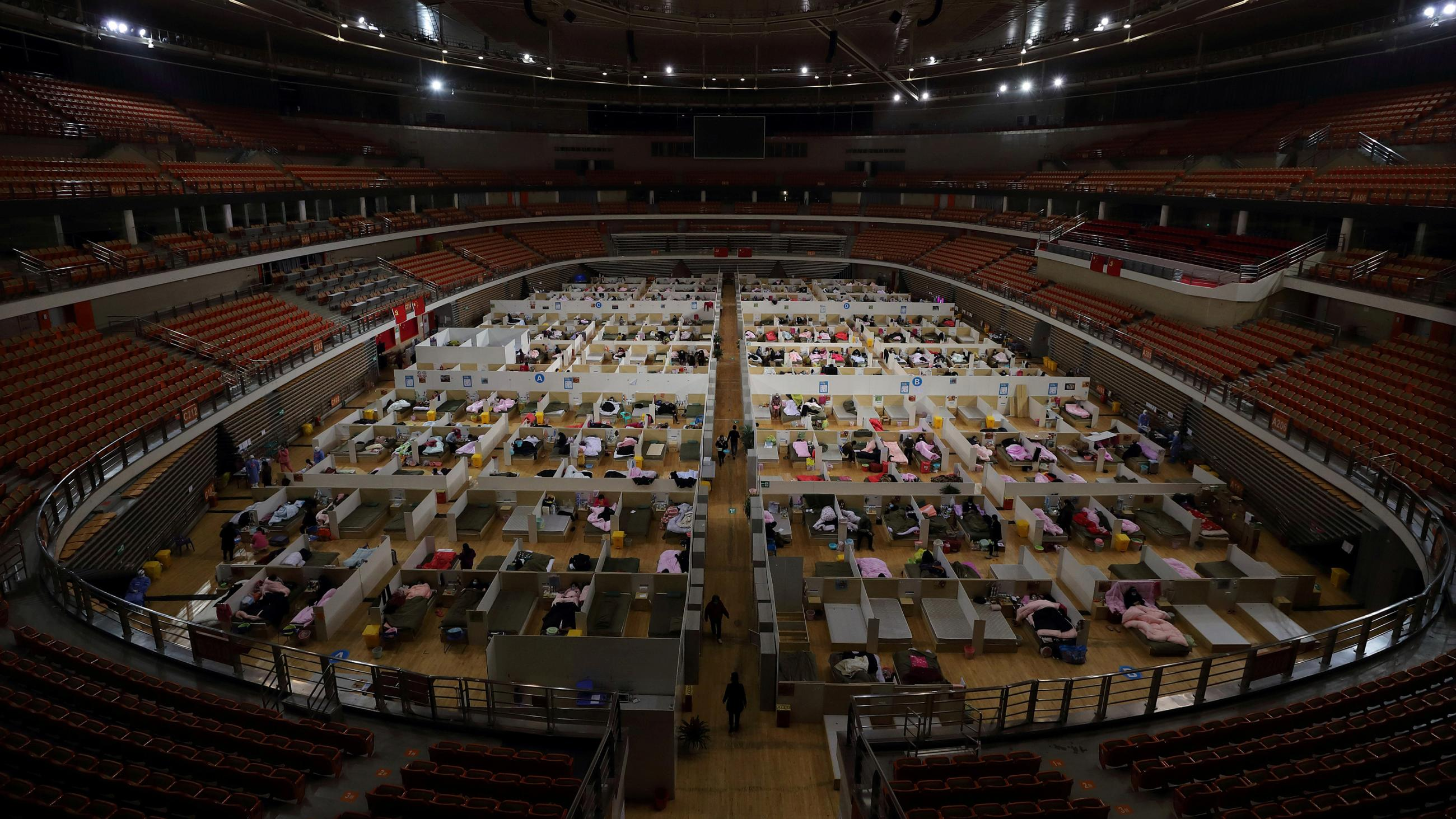 Picture shows a stadium with empty seats and a floor packed with patients resting on mats.